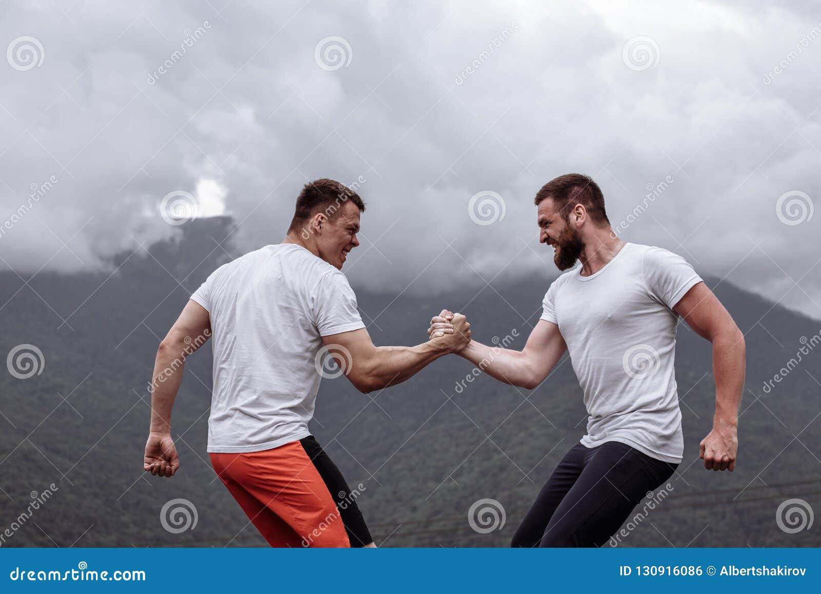 Zwei kaukasische Athleten in messenden Kräften der sportiven Abnutzung Training am im Freien