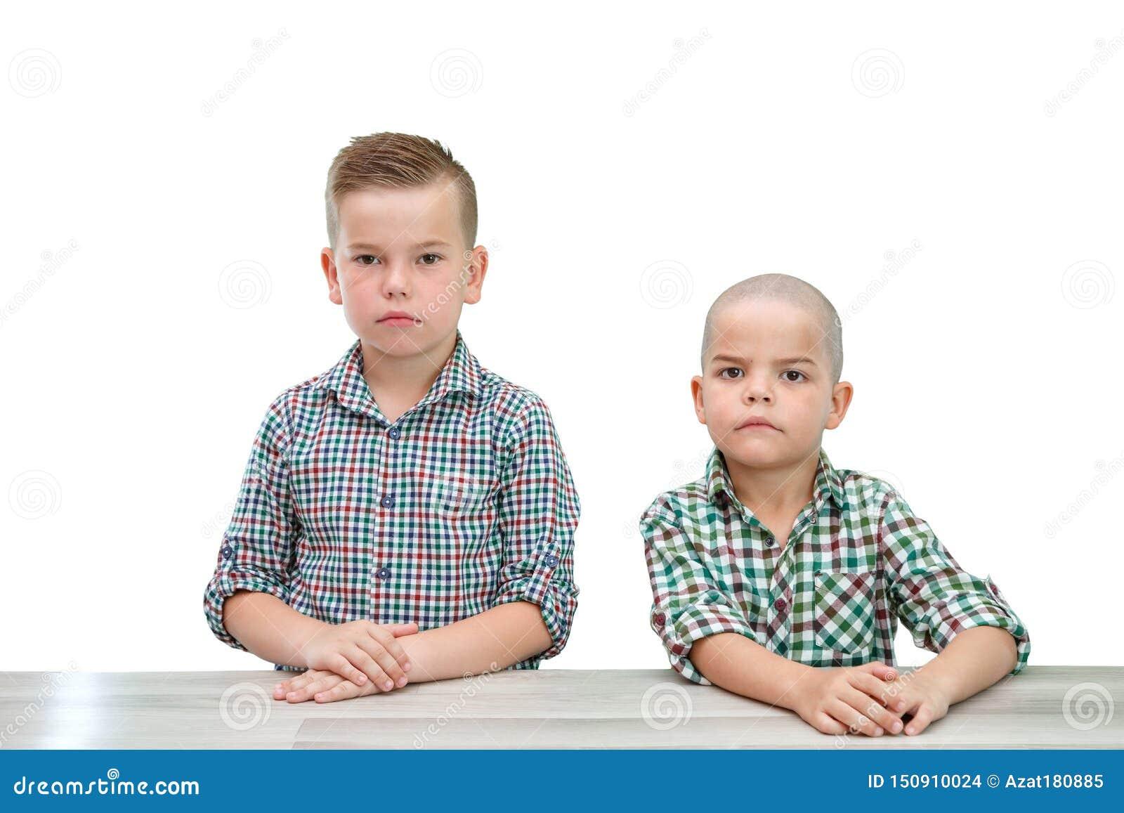 Zwei kaukasische Jungen, Brüder in den karierten Hemden, die auf einem hellen lokalisierten Hintergrund aufwerfen Untersuchung di