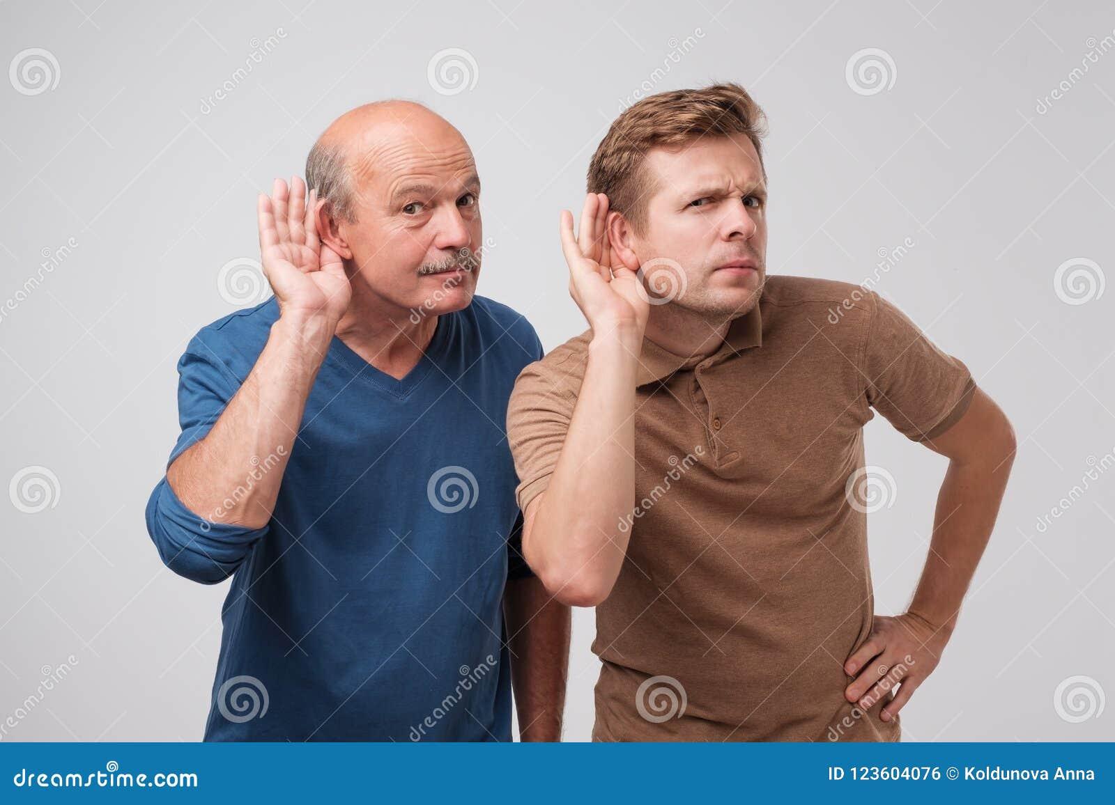 Zwei kaukasische Männer, die mit der Hand auf dem Ohr lokalisiert auf einem weißen Hintergrund hören Sprechen Sie bitte laut