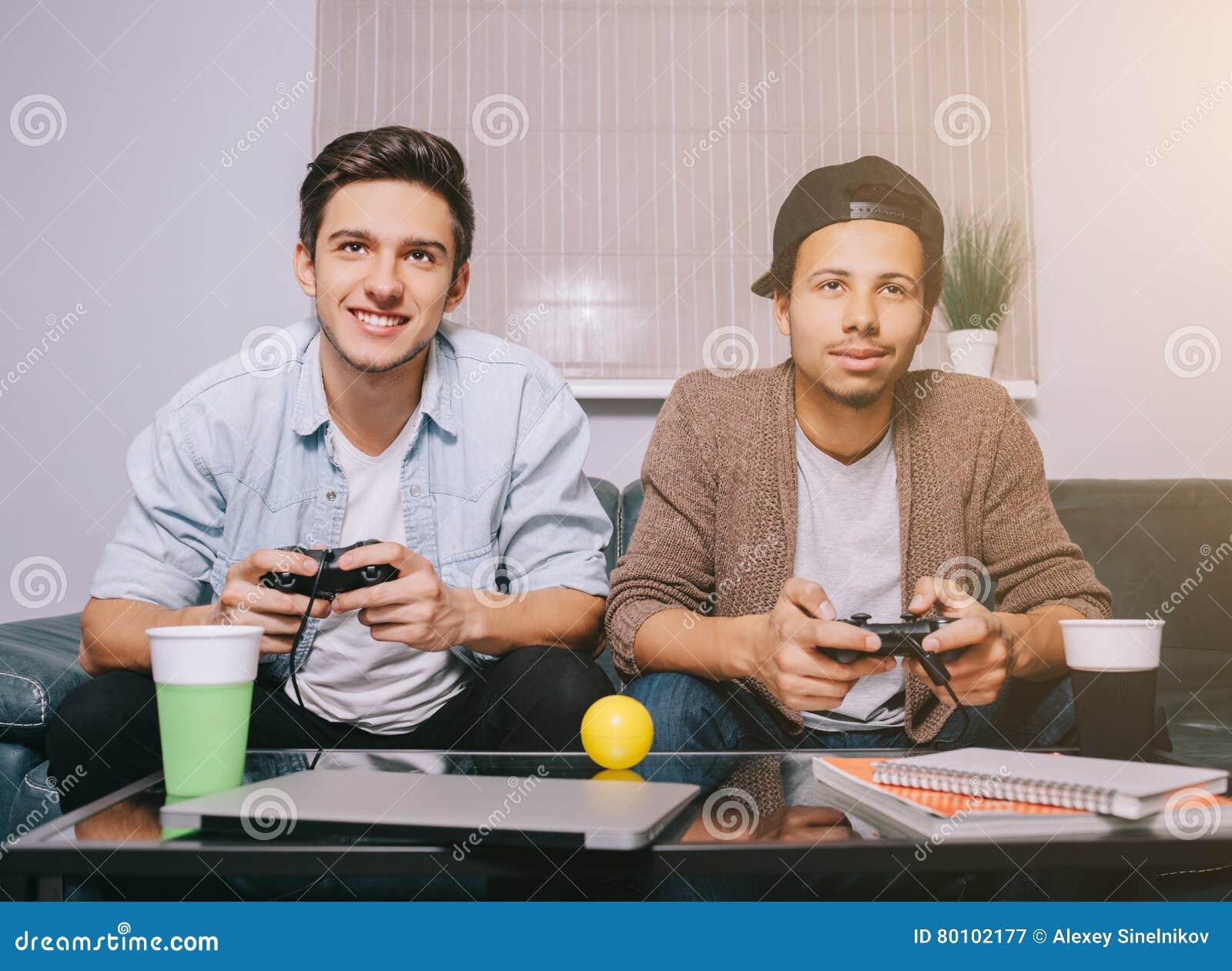 Zwei Kerle, die auf der Konsole sitzt auf der Couch spielen