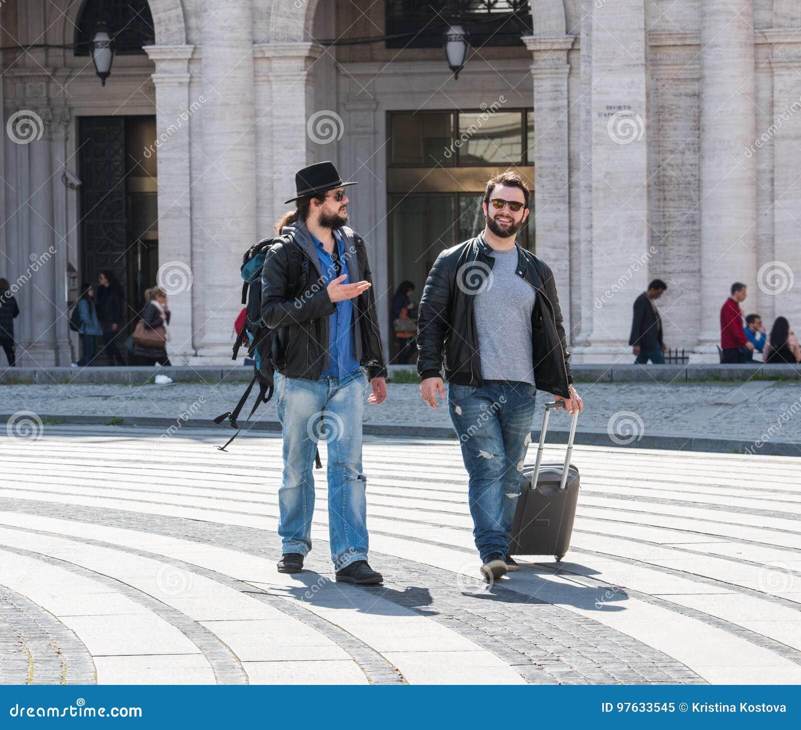Zwei Kerle gehen durch die Straßen von Genua, Italien und schauen herum und miteinander sprechen