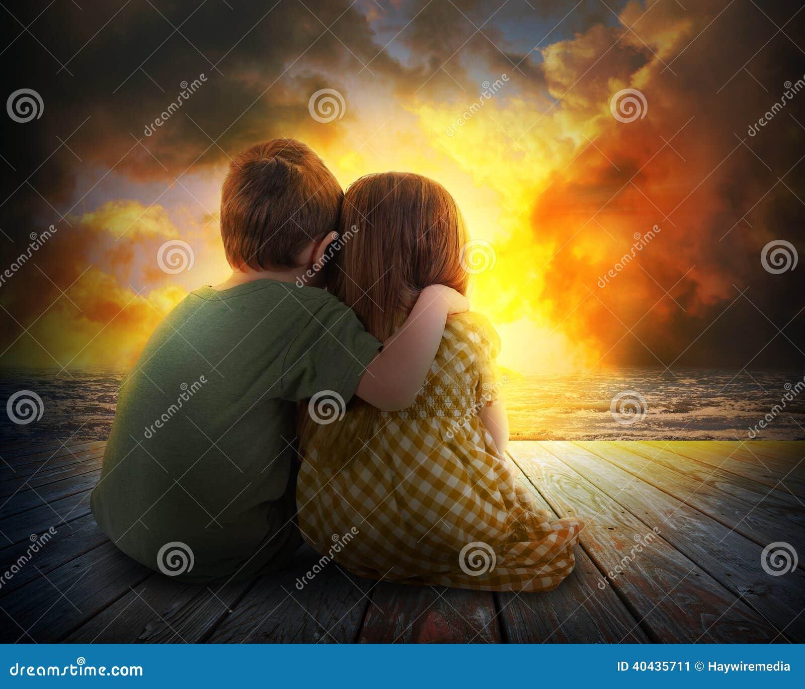 Zwei Kinder, die Sommer-Sonnenuntergang aufpassen