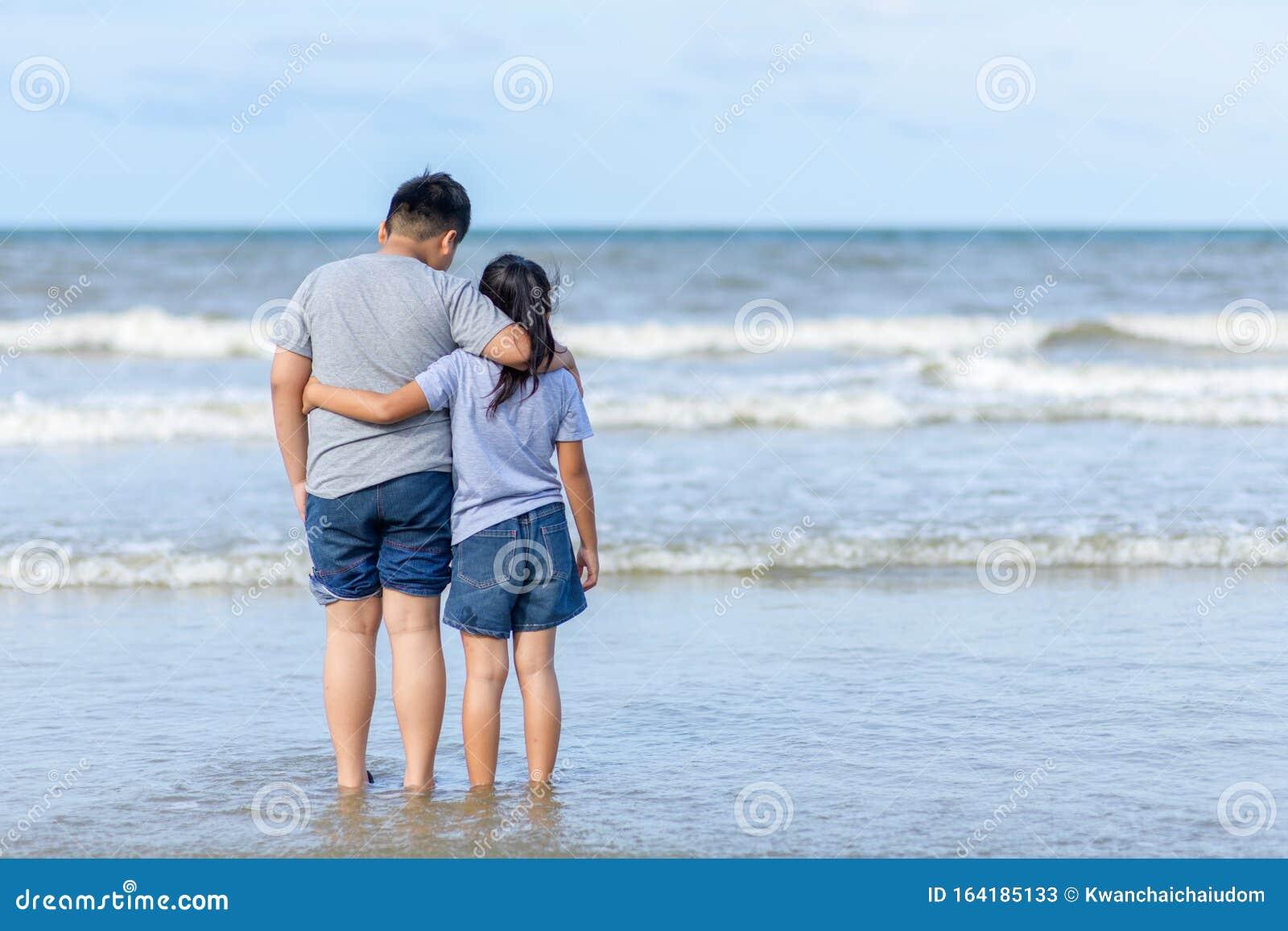 zwei kinder, die am strand spazieren, im urlaub fahren