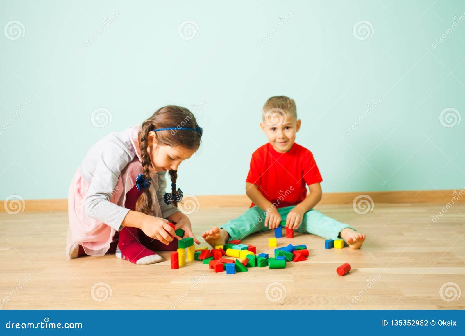 Zwei Kinder, die zu Hause mit Holzklötzen spielen