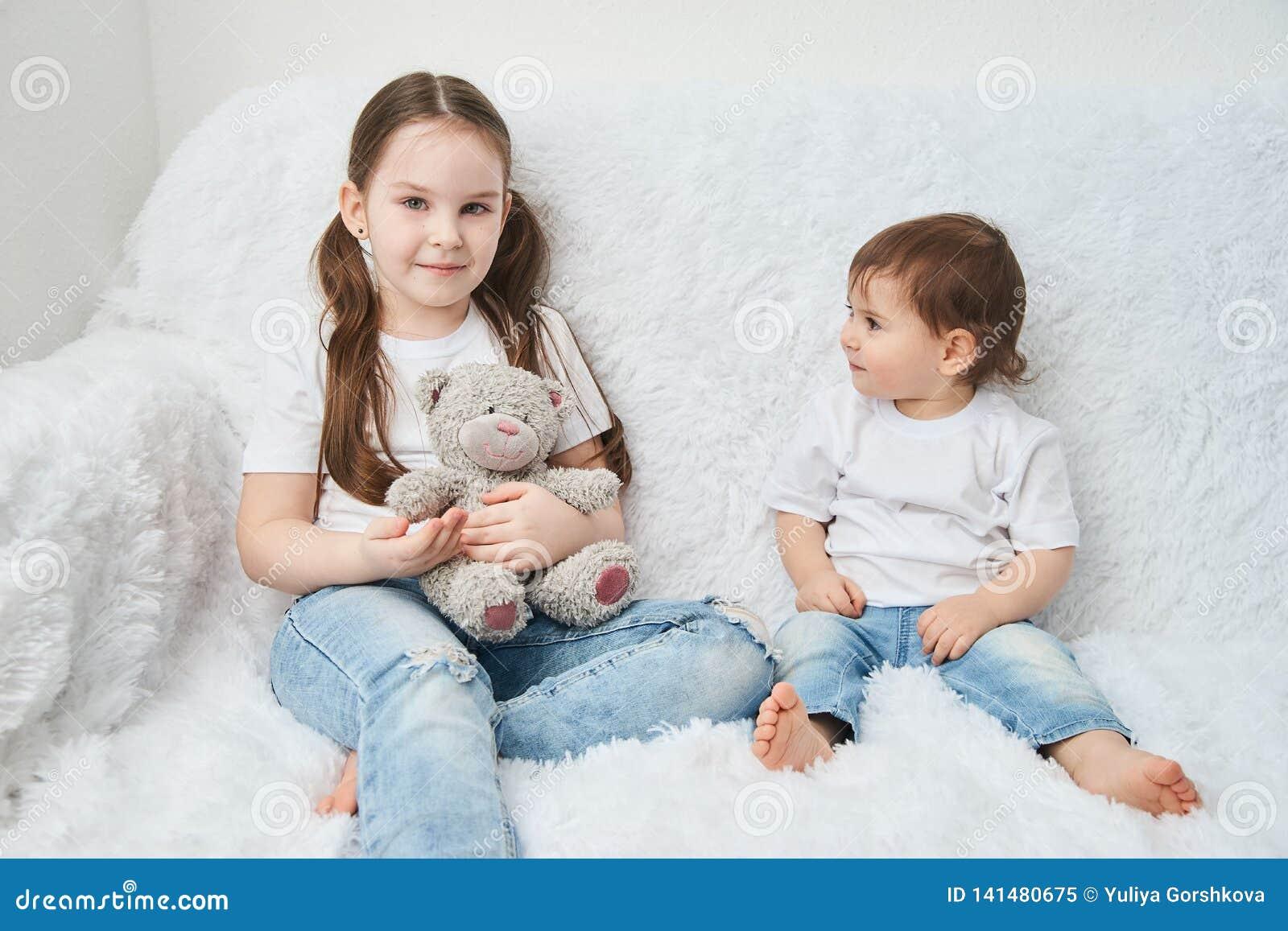 Zwei Kinder, Schwestern sitzen auf einem weißen Sofa in den weißen T-Shirts und in den Blue Jeans Weicher Plüschbär