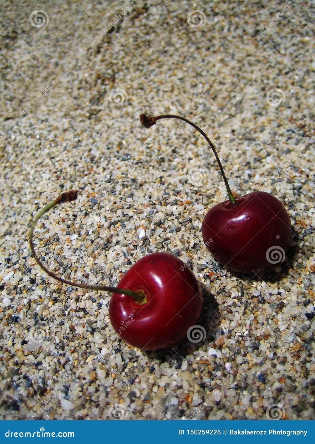 Zwei Kirschen auf dem Strandmakrohintergrund