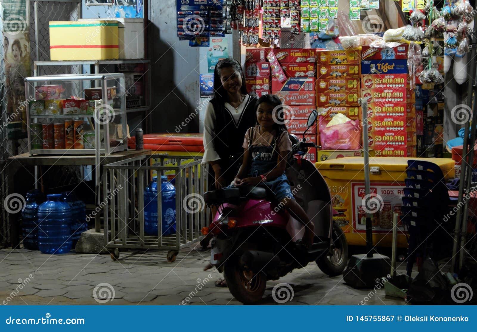 Zwei kleine kambodschanische Mädchen nahe einem Bewegungsroller Wenig Straßengeschäft Gl?ckliche l?chelnde Kinder