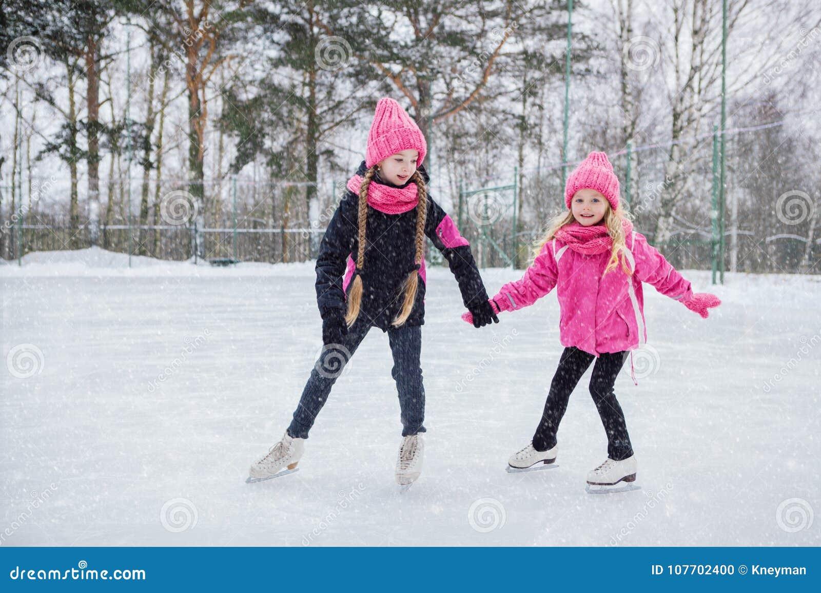Zwei kleine lächelnde Mädchen, die auf Eis in der rosa Abnutzung eislaufen