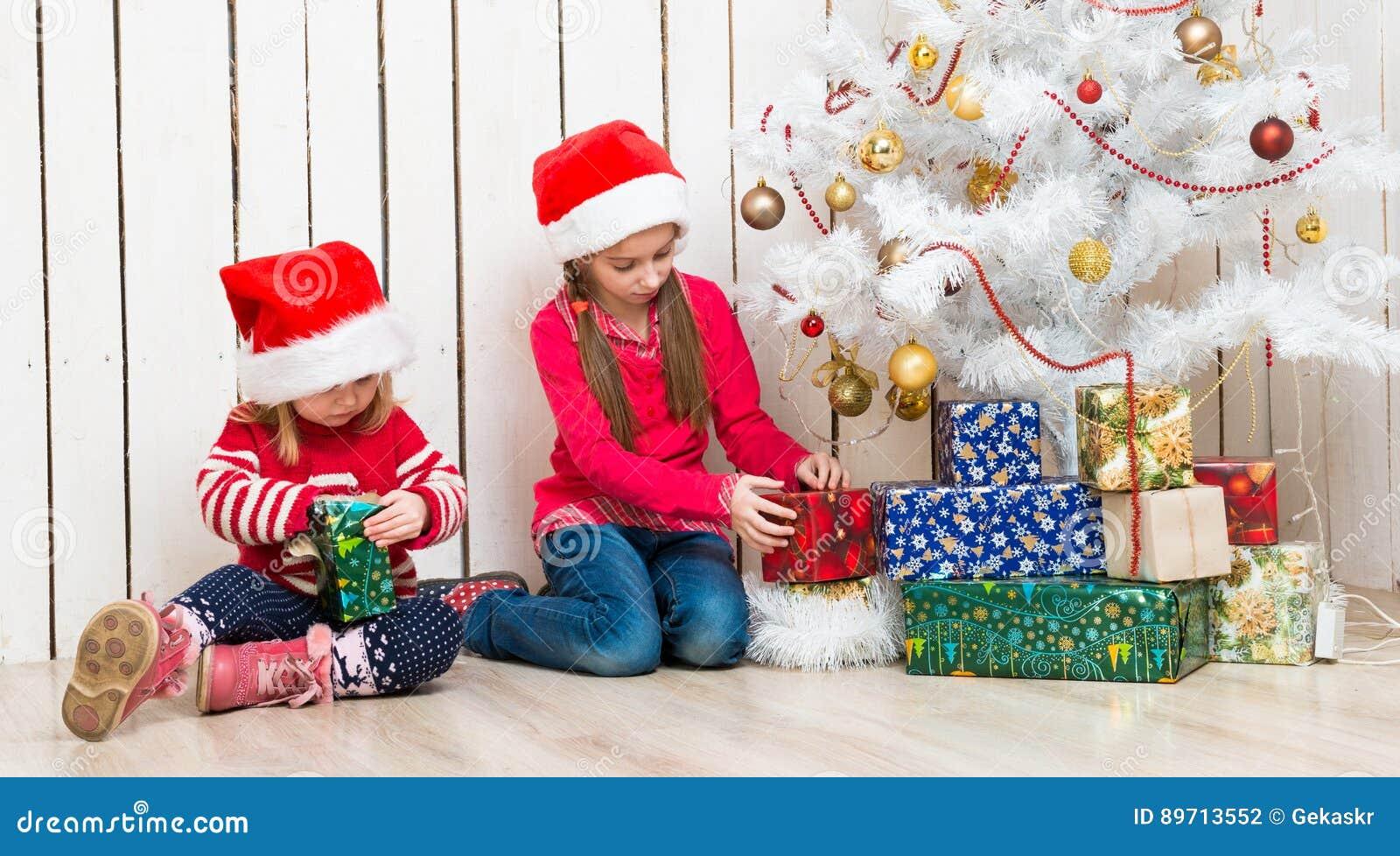 Zwei Kleine Mädchen öffnen Die Weihnachtsgeschenke, Die Auf Dem ...
