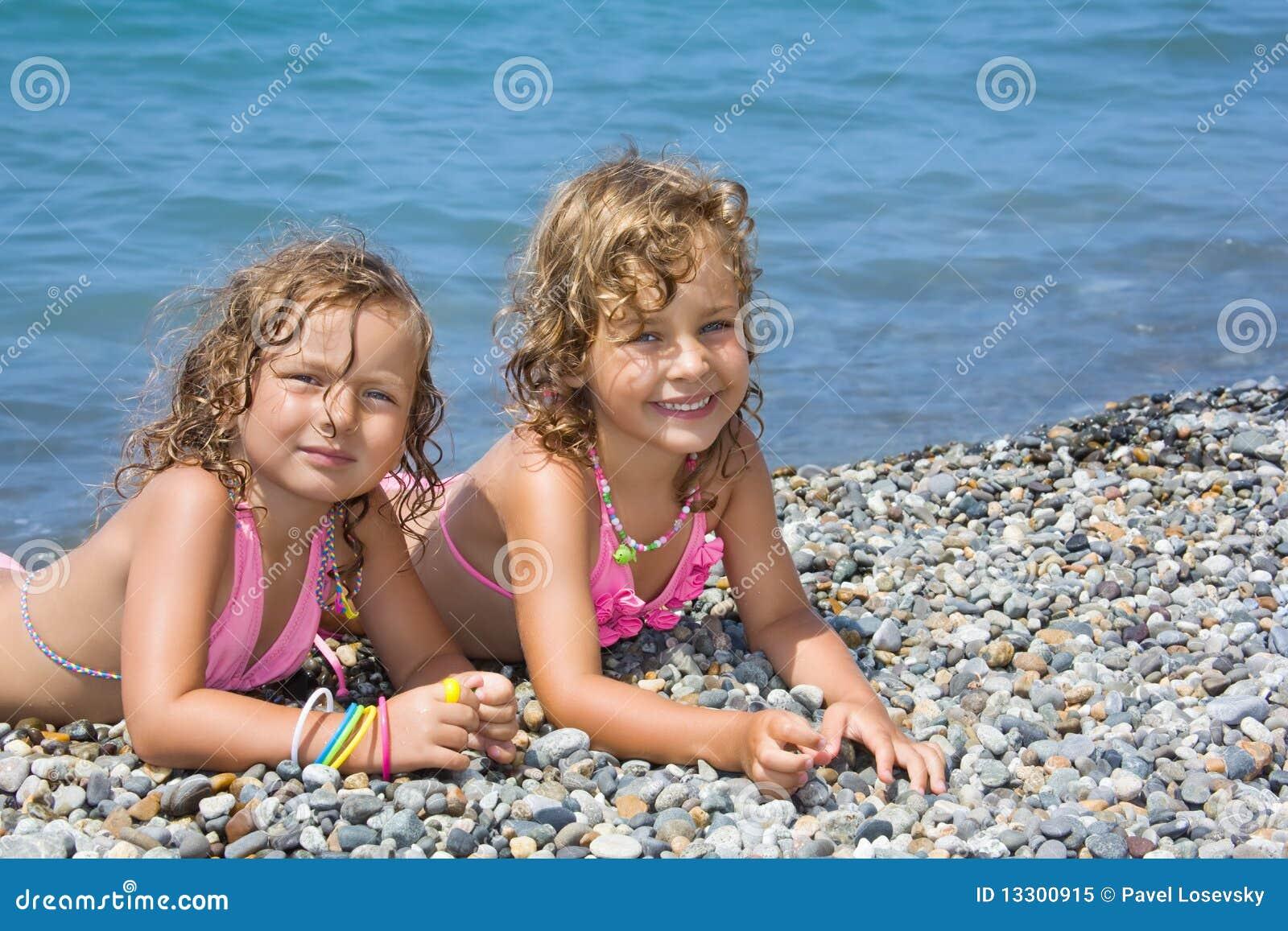 Zwei kleine m dchen die auf steinigem strand liegen lizenzfreies stockfoto bild 13300915 - Kleine teen indelingen meisje ...