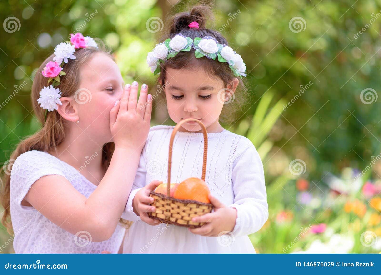 Zwei kleine Mädchen im weißen Kleid hält einen Korb mit frischer Frucht in einem Sommergarten