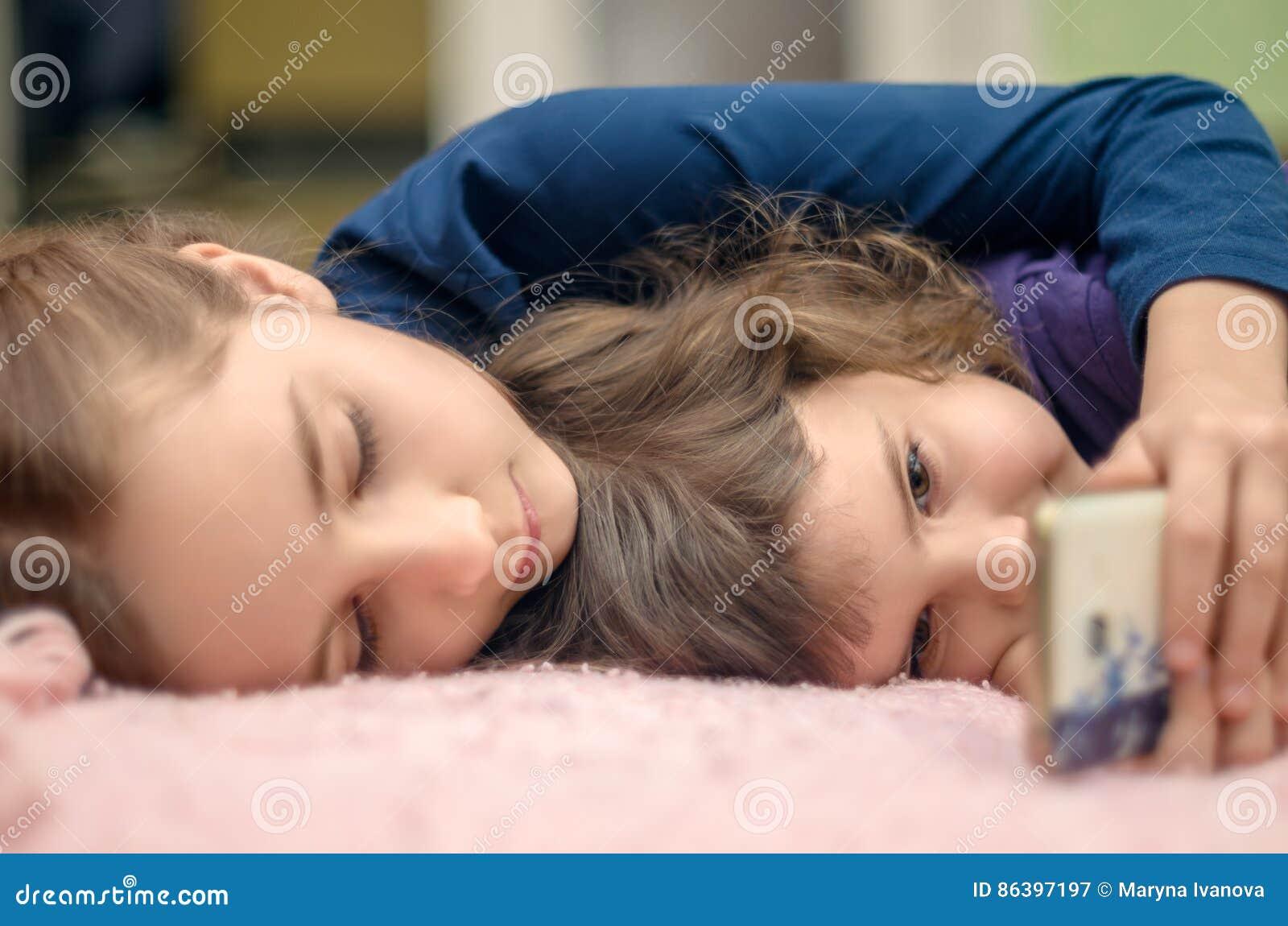 Zwei kleine Mädchen mit dem Smartphone, der zu Hause auf Bett und playin liegt
