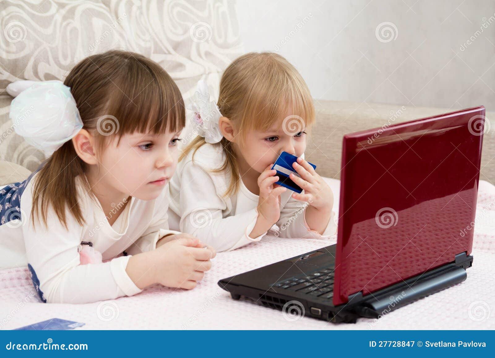 Zwei kleine Mädchen sind mit einem Laptop