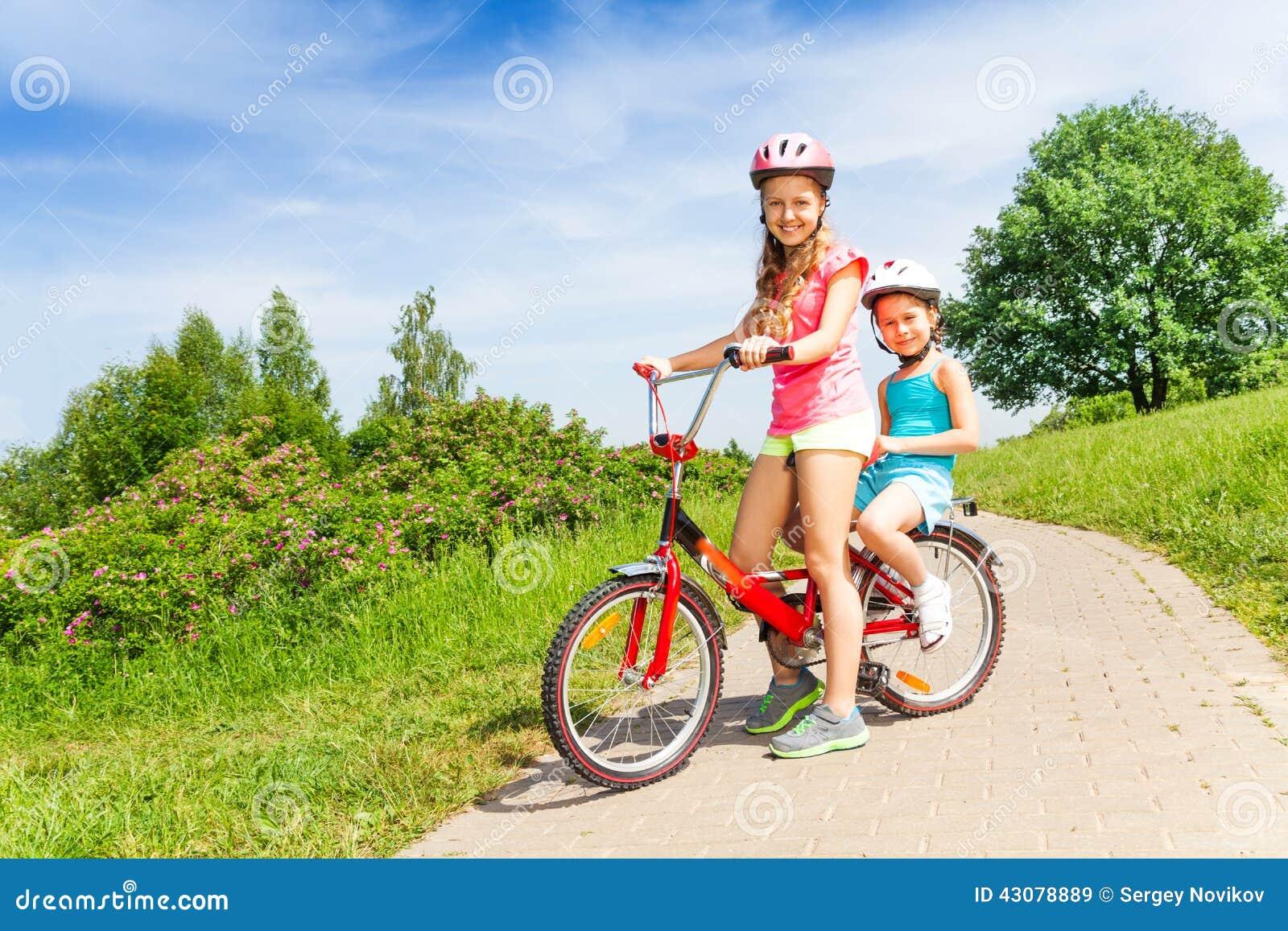 zwei kleine m dchen sitzen auf einem fahrrad stockfoto. Black Bedroom Furniture Sets. Home Design Ideas