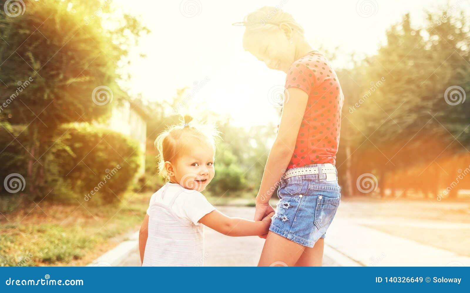Zwei kleine Schwestern, die zusammen in Sommerstadtpark gehen Familienwertkonzeptfoto