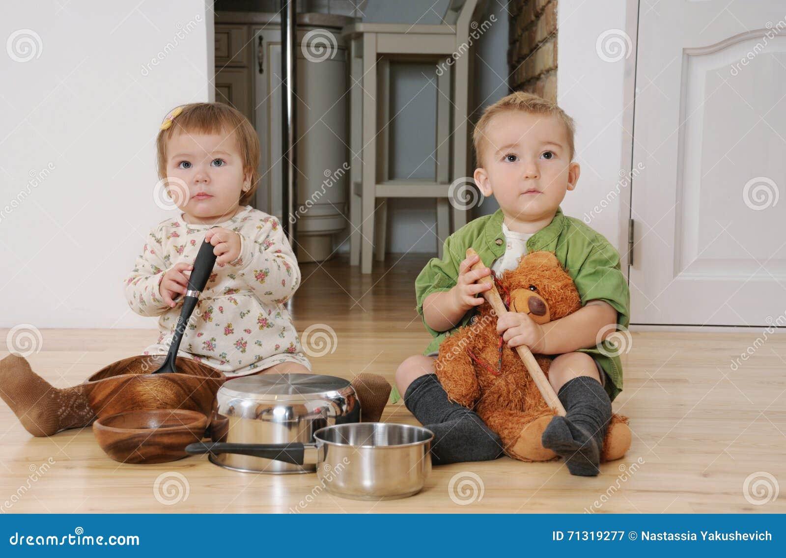 Zwei Kleinkinder Der Junge Und Mädchen, Die Auf Der Küche Sitzen ...