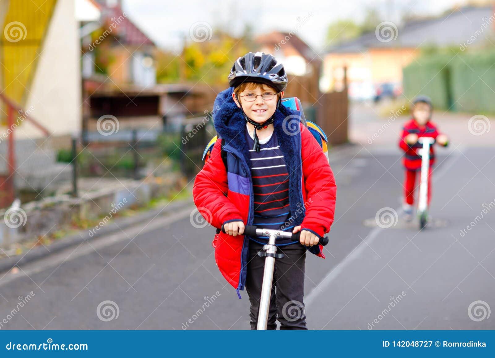 Zwei Kleinkindjungen, die auf dem Weg auf Stoßroller nach oder von Schule fahren Schüler von 7 Jahren, die durch Regen fahren