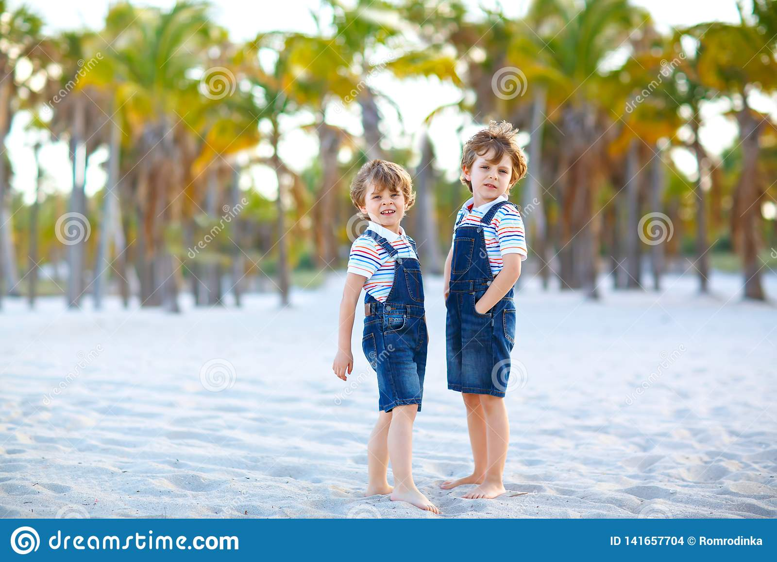 Zwei Kleinkindjungen, die Spaß auf tropischem Strand, glückliche beste spielende Freunde, Freundschaftskonzept haben Geschwisterb