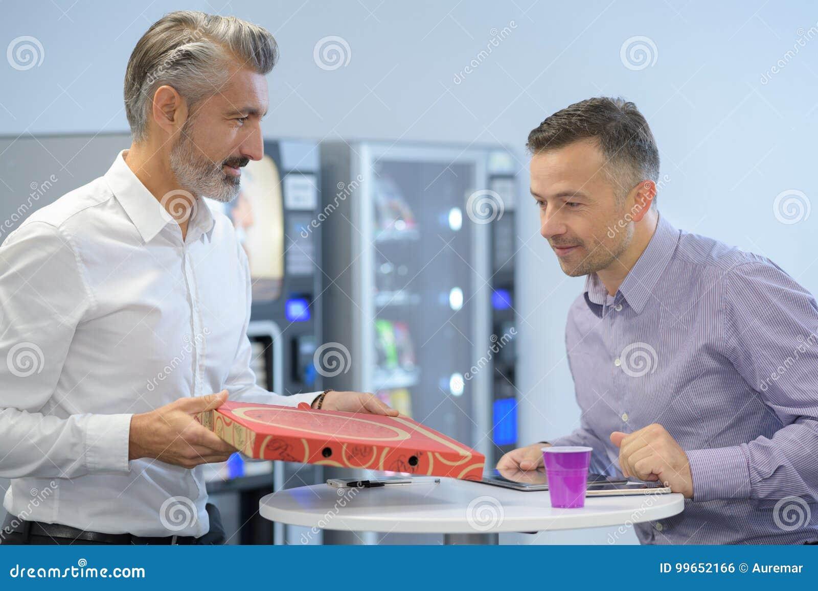 Zwei Kollegen Die Pizza Wahrend Der Mittagspause Im Buro Essen