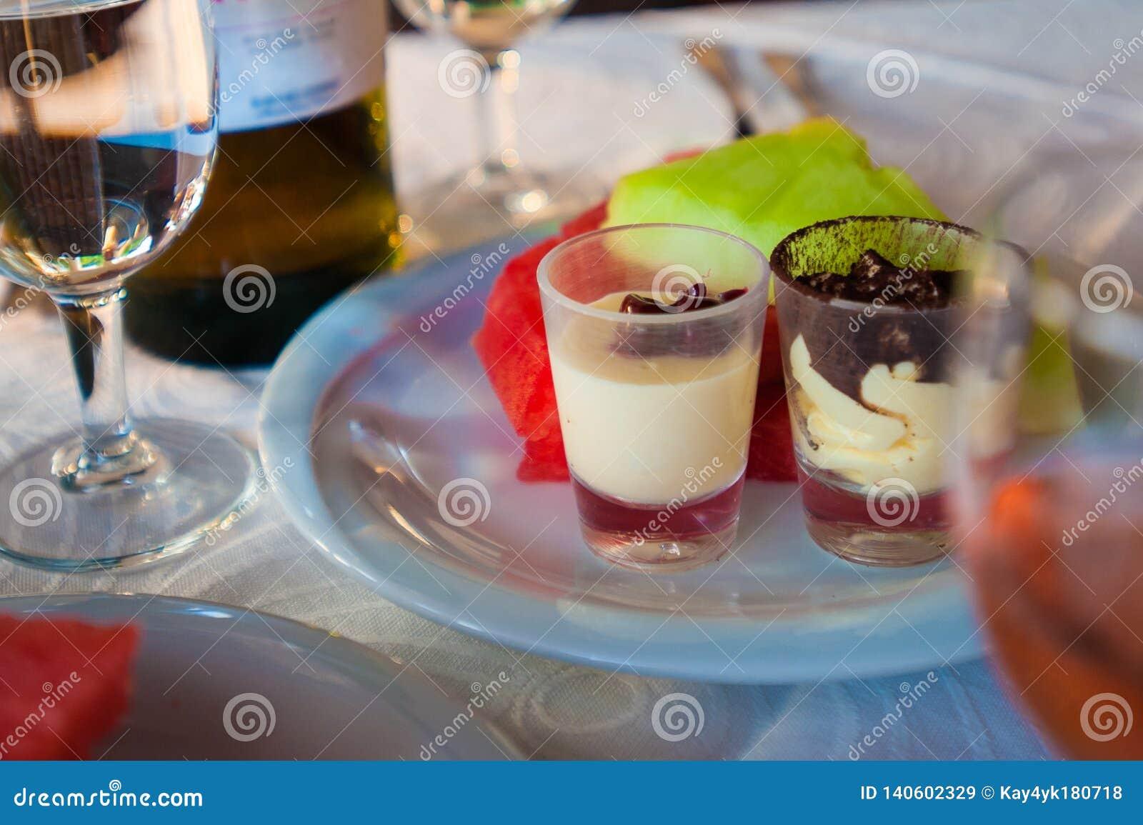 Zwei Kuchen auf einer Platte mit einem Glas Wein und Frucht