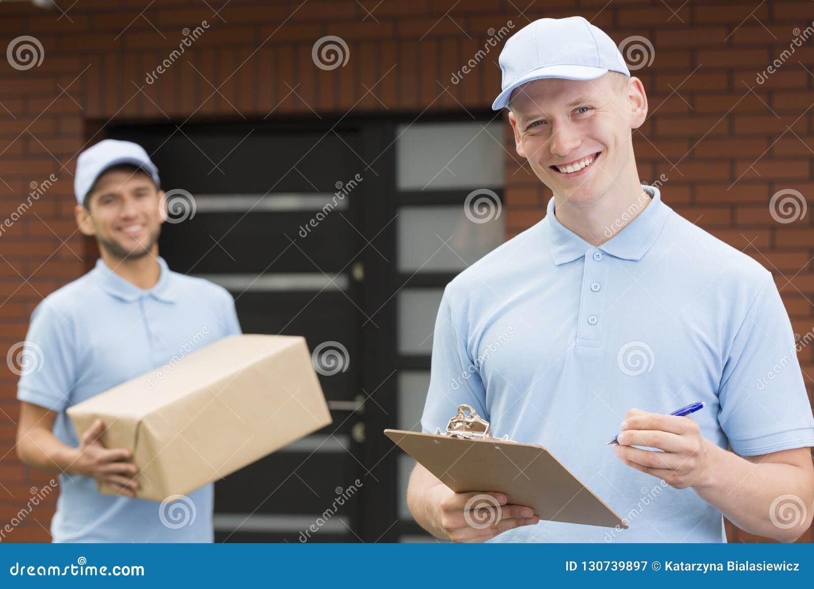 Zwei Kuriere in den blauen Uniformen, die vor einem Haus stehen und mit Lieferung warten