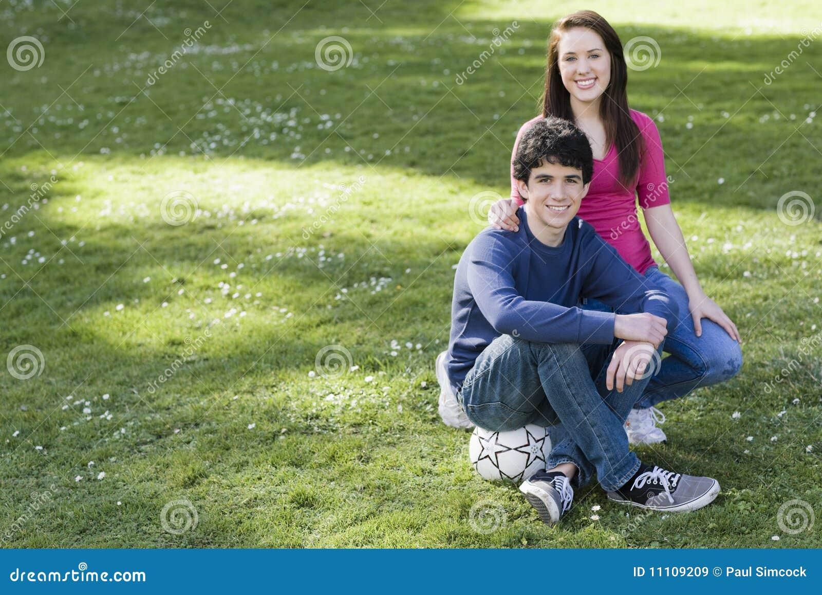 Zwei lächelnde Jugendliche mit Fußball-Kugel