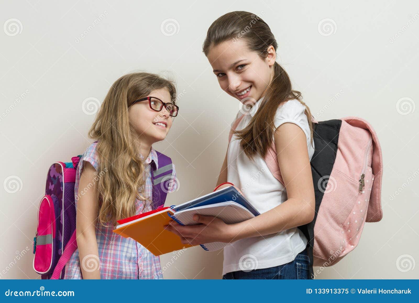 Zwei lächelnde Mädchen mit Schultaschen Altes in der Schule sprechen der Schulmädchen 7 und 10 Jahre