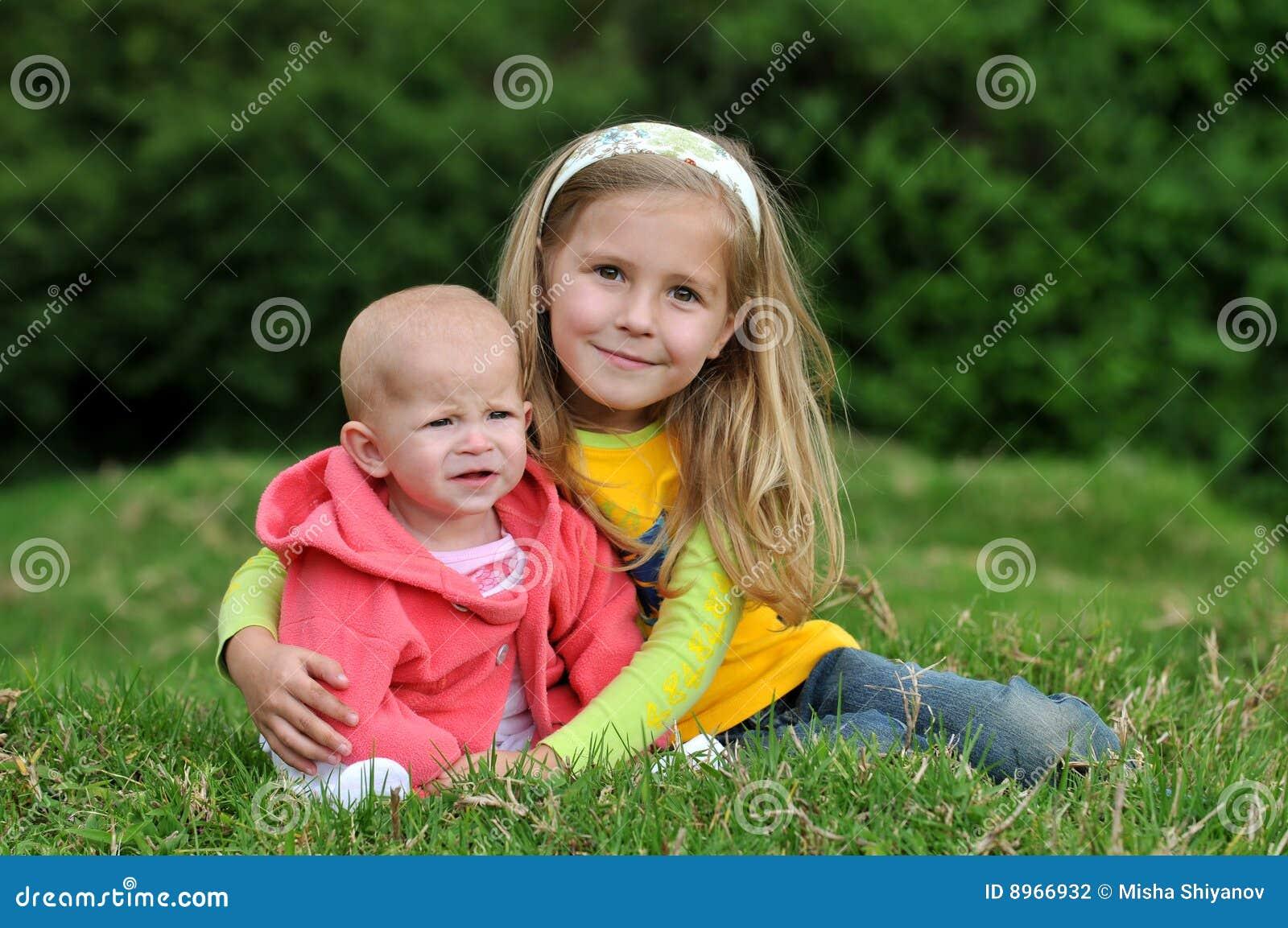 Zwei lächelnde Schwestern auf dem Rasen
