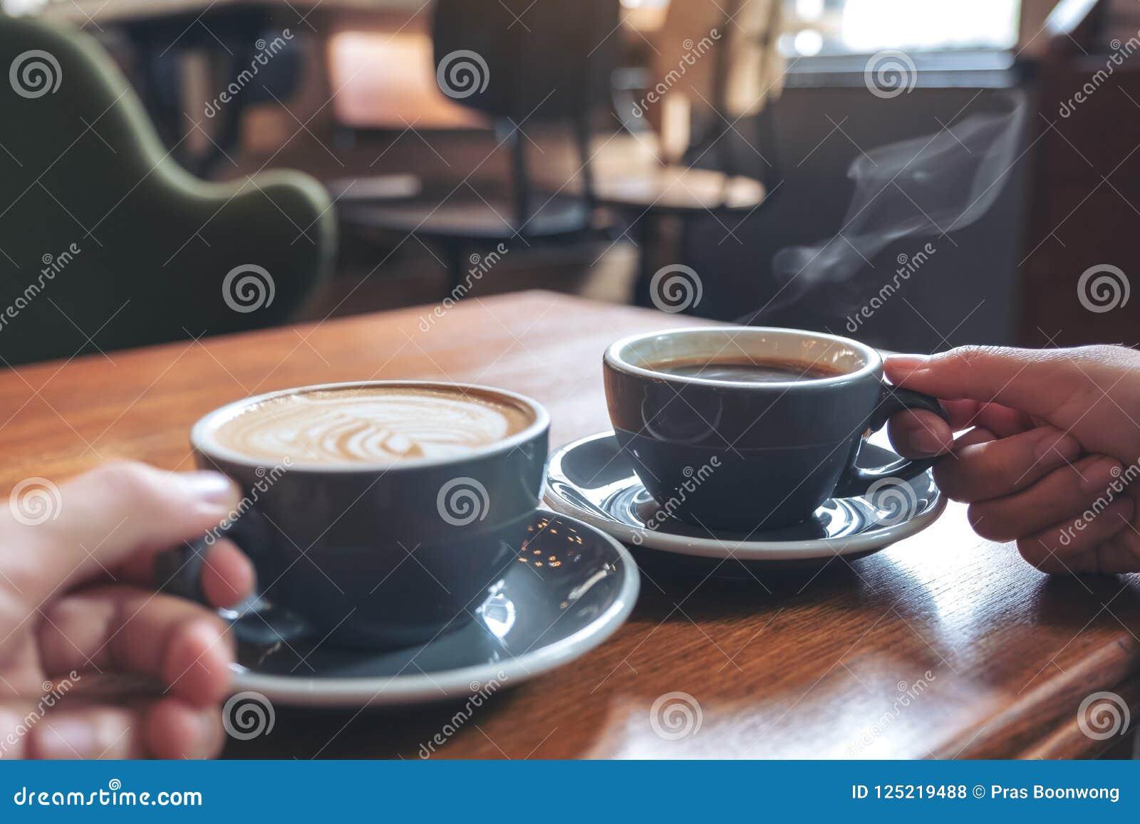 Zwei Leute ` s übergibt das Halten von Schalen des Kaffees und der heißen Schokolade auf Holztisch im Café