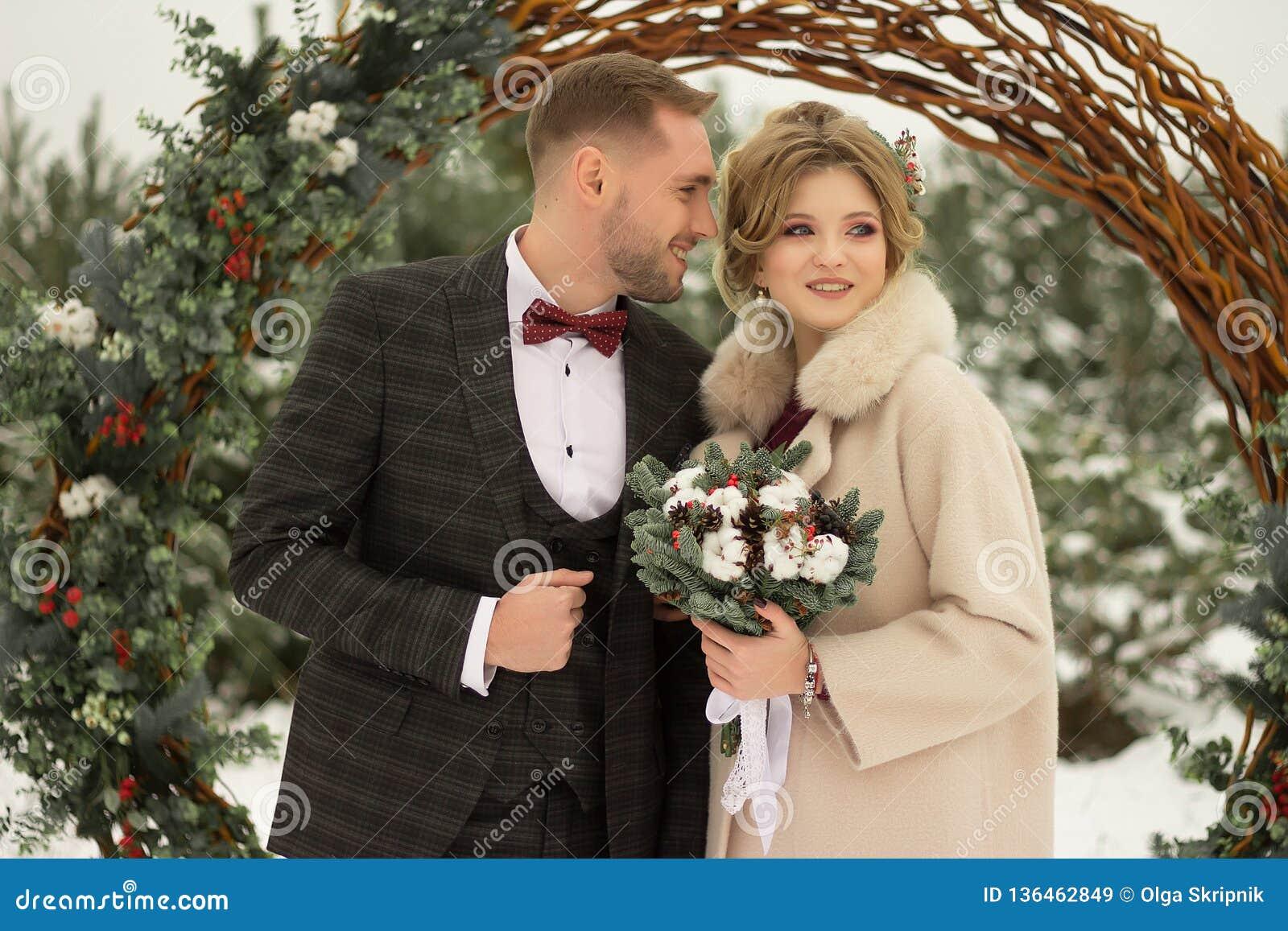Zwei Liebhaber, ein Mann und eine Frau, eine Hochzeit im Winter Braut- und Bräutigamliebe gegen den Hintergrund des Dekors und de