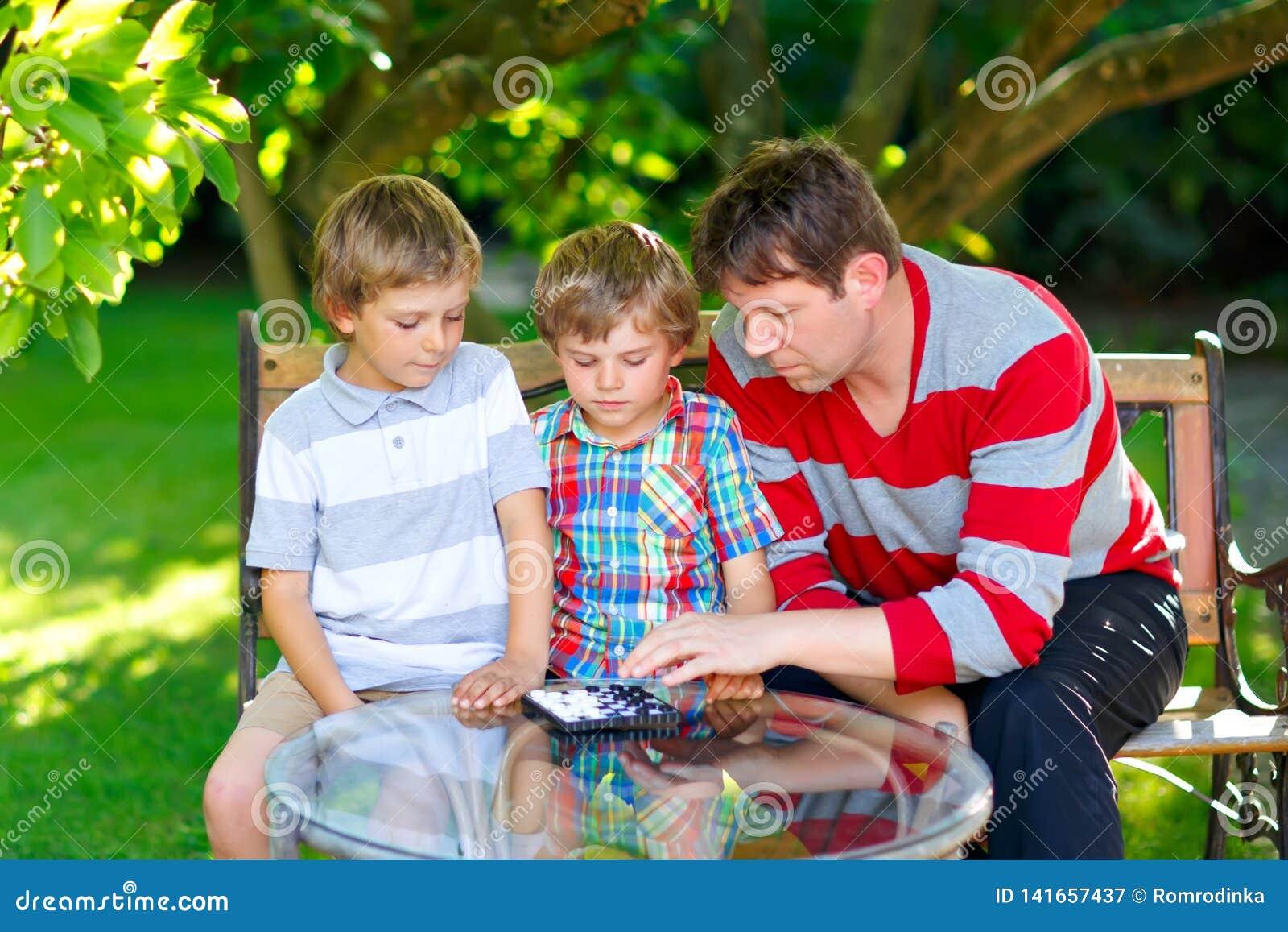 Zwei lustige hübsche Kinderjungen und junger Vater, die zusammen Kontrolleurspiel spielen Söhne, Geschwisterkinder und Vatiausgab