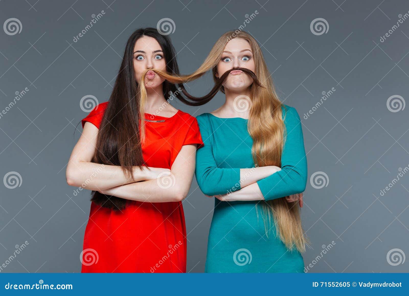 Zwei lustige Mädchen, die Schnurrbart mit ihrem Haar herstellen