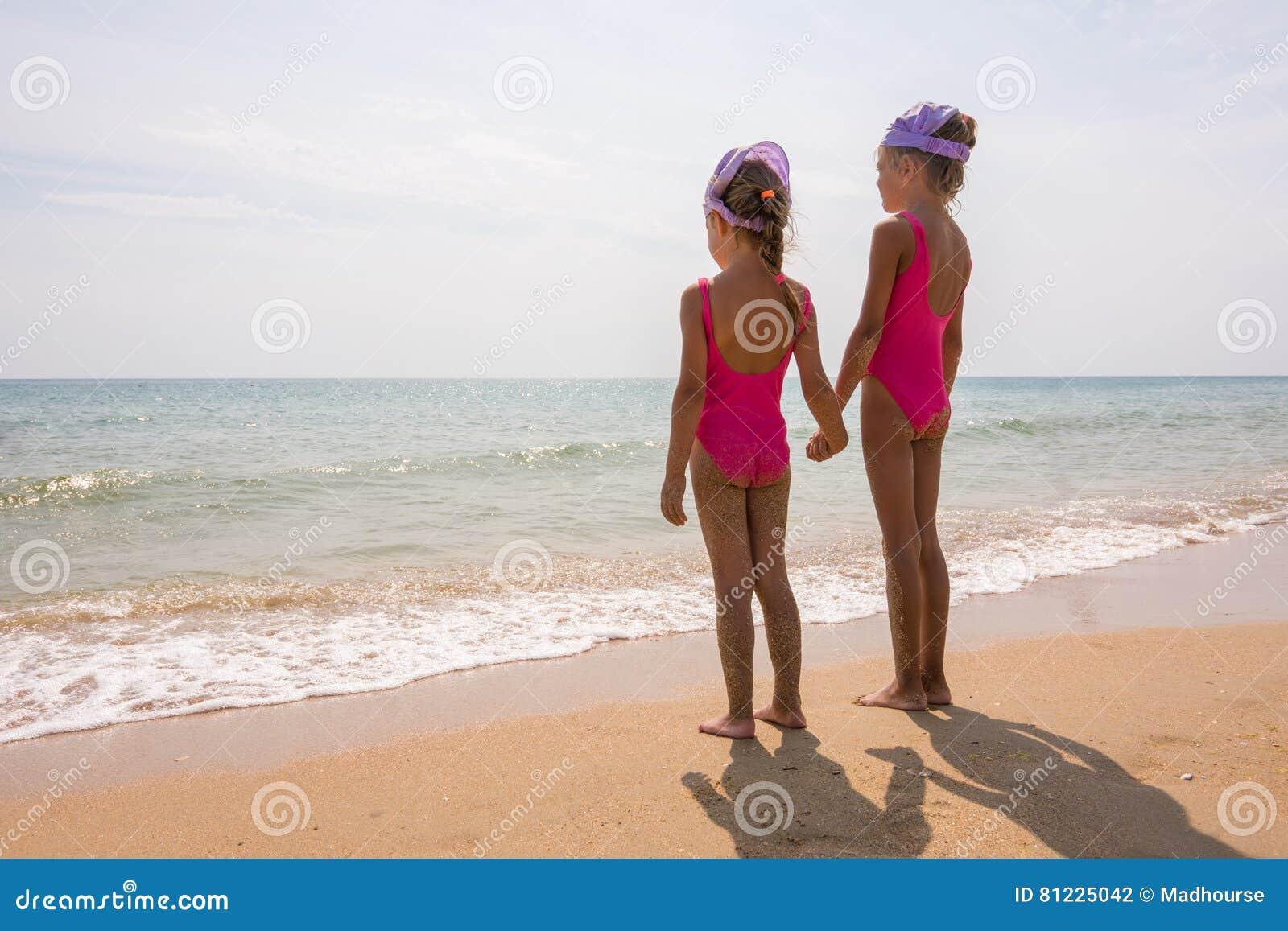 Zwei Mädchen in den Badeanzügen, die auf Strand und Blick am Horizont stehen