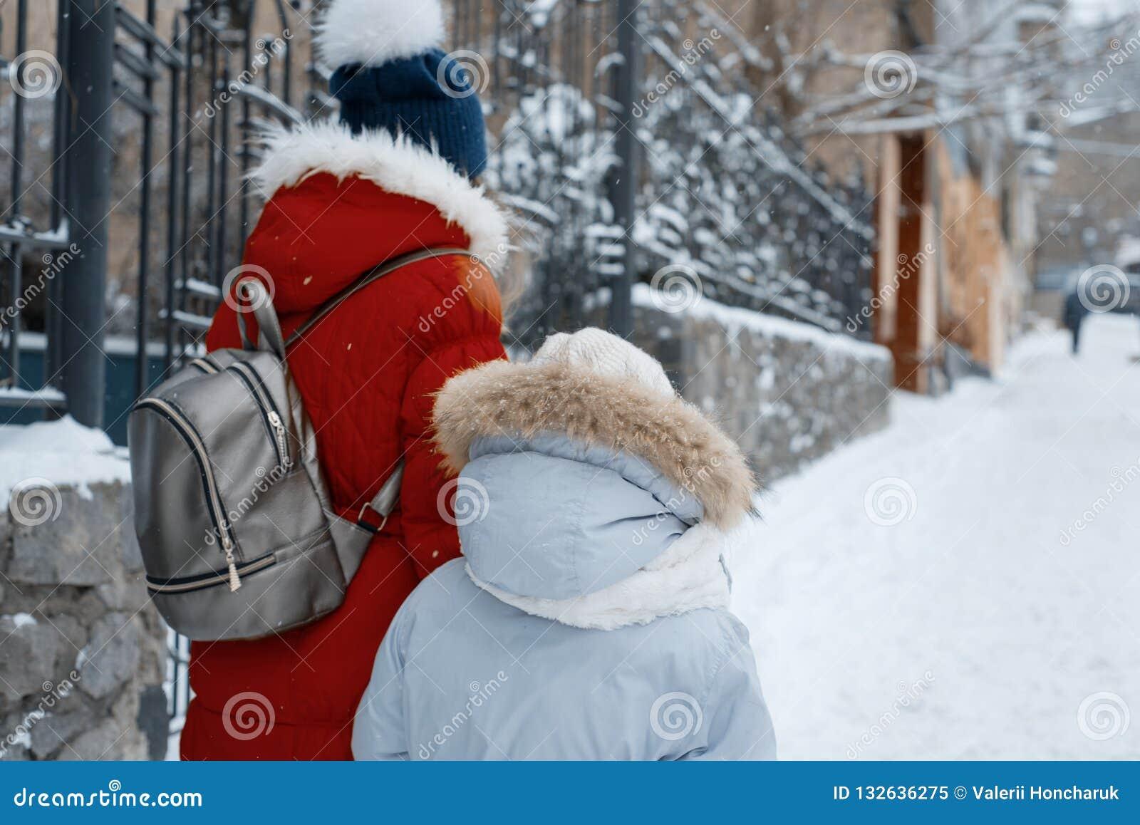 Zwei Mädchen, die entlang die schneebedeckte Straße des Winters der Stadt gehen, Kinder sind Händchenhalten, hintere Ansicht