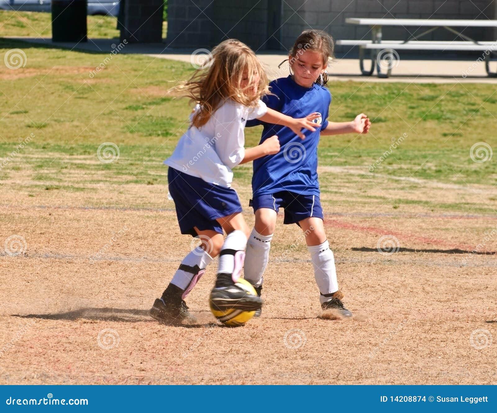 Zwei Mädchen, die für die Kugel/den Fußball kämpfen