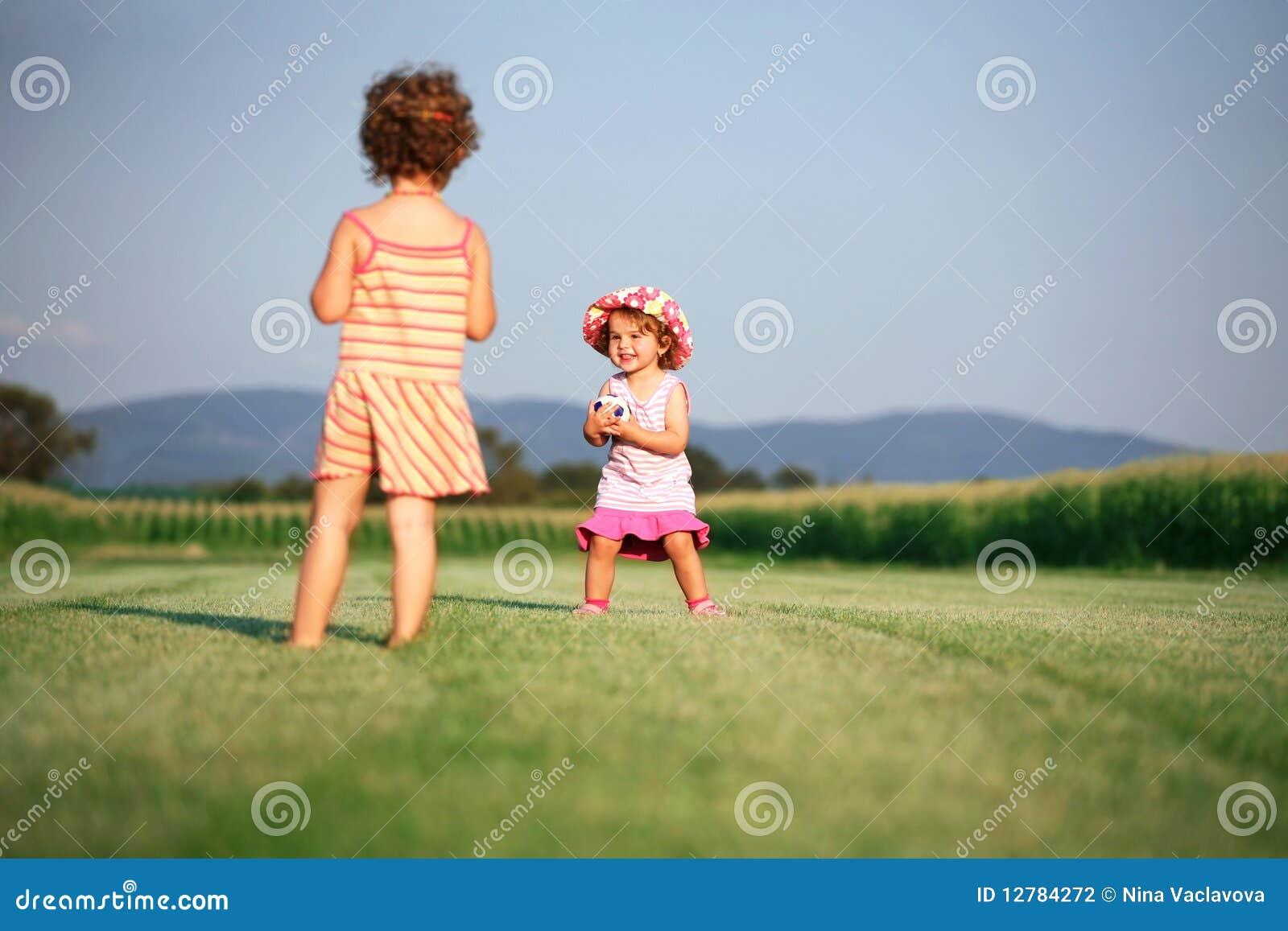 Zwei Mädchen, die mit Kugel spielen