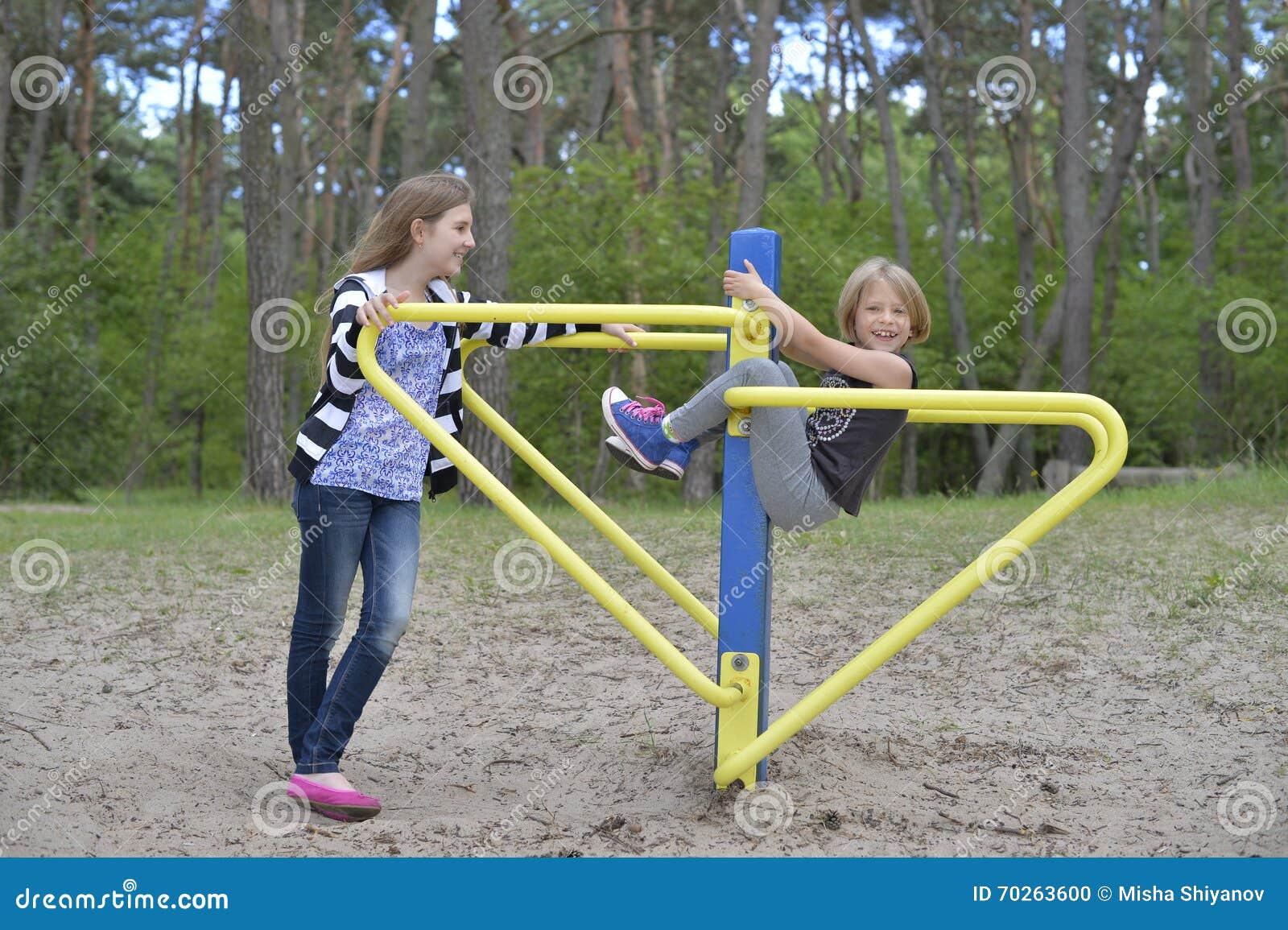 Zwei Mädchen spielen auf dem Spielplatz auf der gelbes Metallanziehungskraft Es ist windig