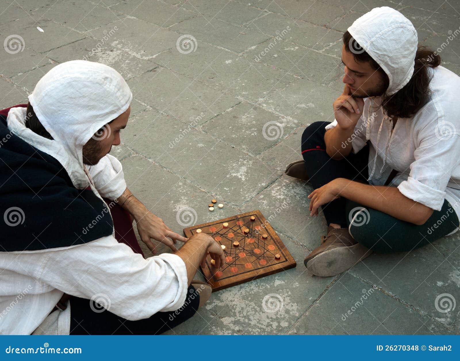 Zwei Männer im Kostüm, das mittelalterliches Brettspiel spielt