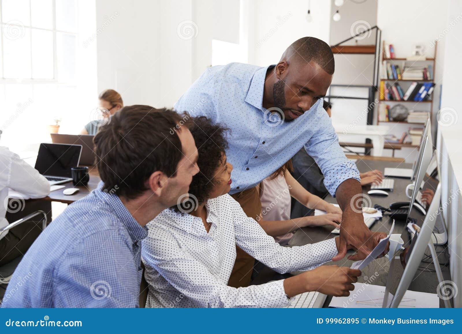 Zwei Männer und eine Frau, die in im Bürogroßraum zusammenarbeitet