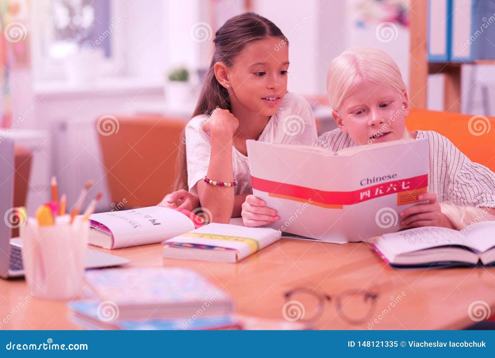Zwei nette Kinder, die ein chinesisches Buch lesen