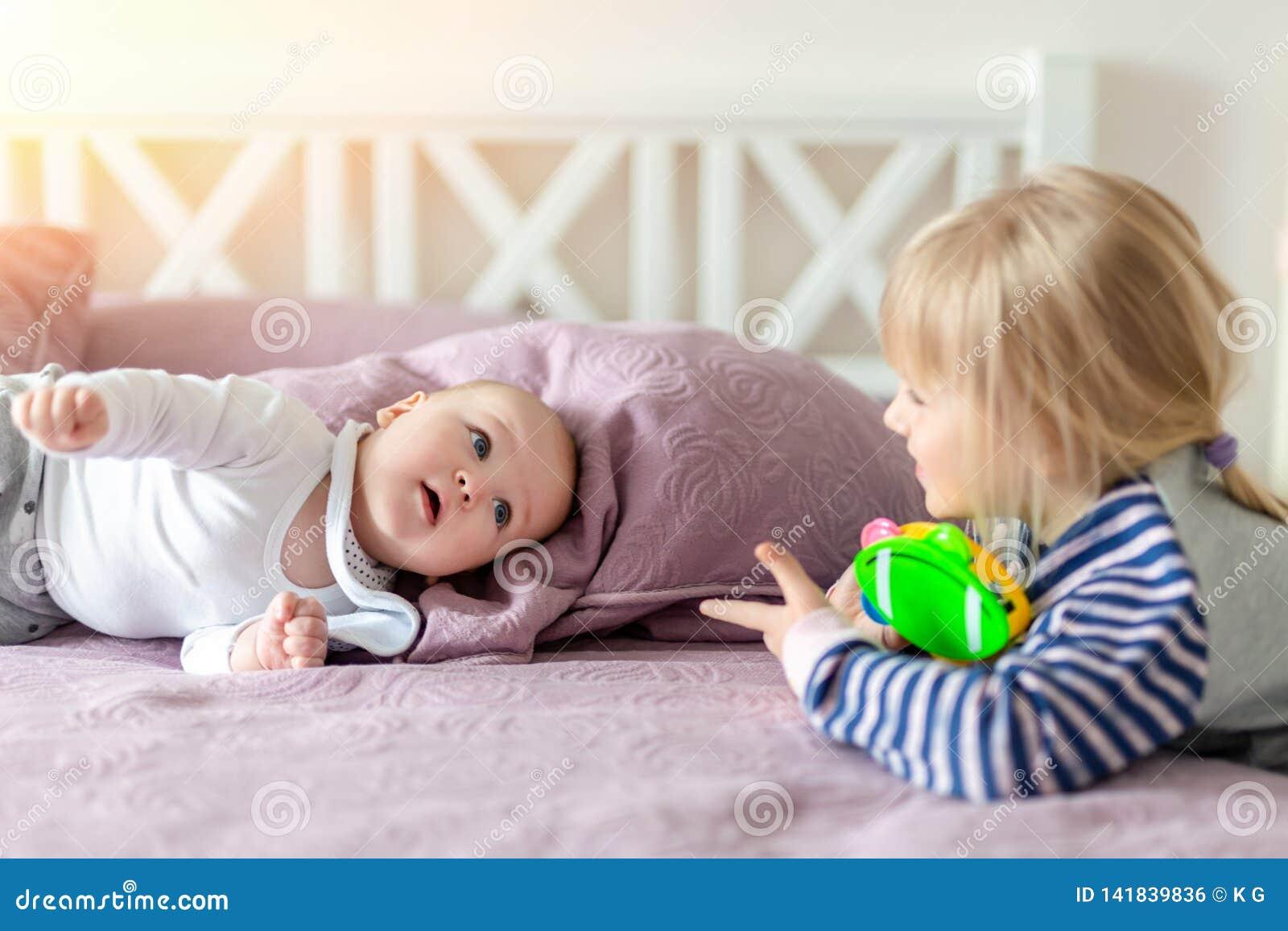 Zwei nette kleine Geschwister, die zusammen auf Bett spielen Schwester und Bruder, die Spaß am Schlafzimmer im Morgen haben Glück