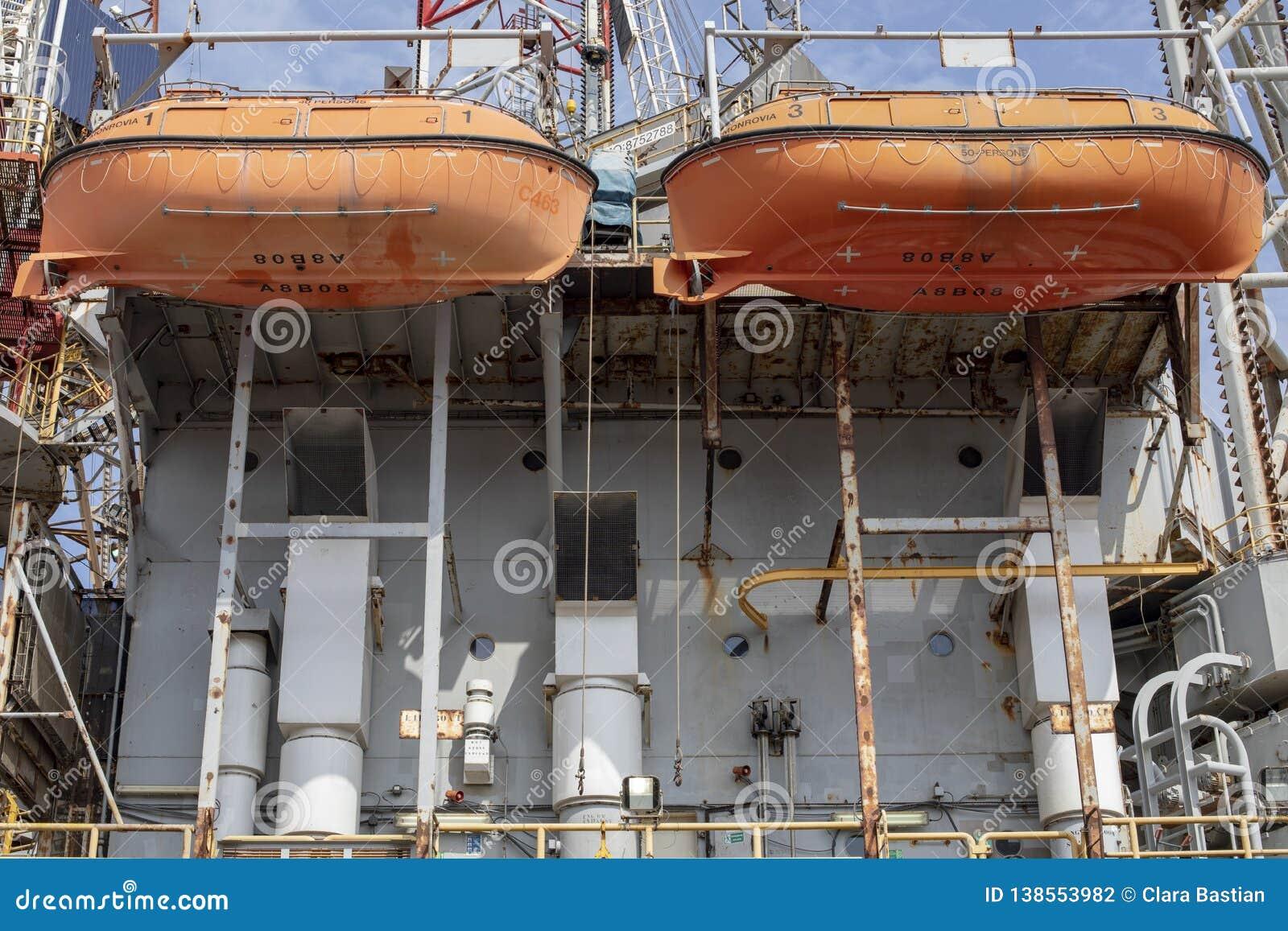 Zwei orange Rettungsboote, die am rostigen Containerschiff hängen