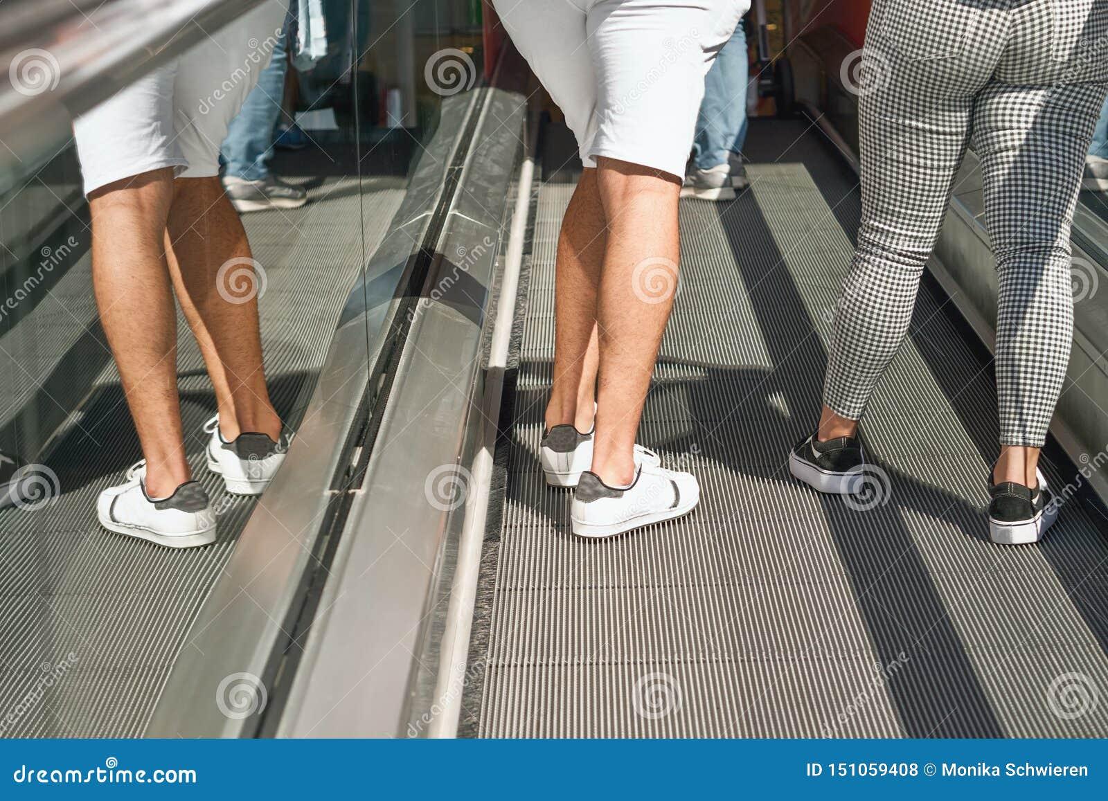 Zwei Personen fahren herauf eine Rolltreppe, nur die Beine sichtbar sind, die linke Person wird widergespiegelt im Glasdeckel