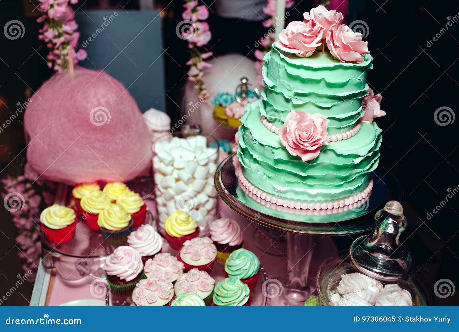 Zwei-planierte Minze färbte Rosen, macarons und Eibische der Hochzeitstorte mit Sahne Schokoriegel in den Farben des kleinen Fing