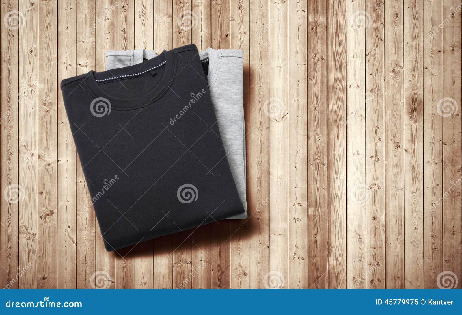 Zwei Pullover, die auf hölzernem Hintergrund liegen