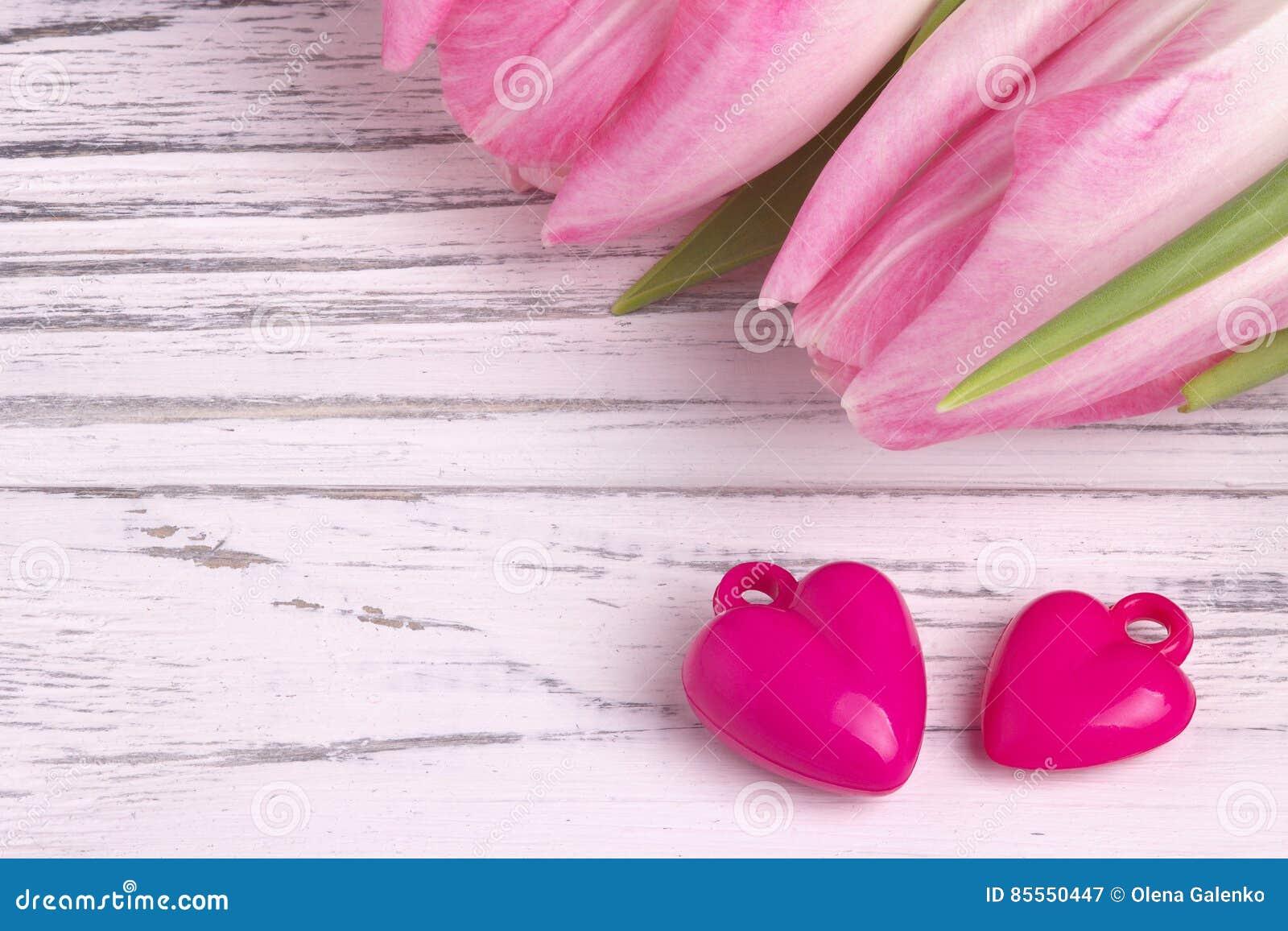Zwei purpurrote Herzen mit rosafarbenen Tulpen auf Weiß malten rustikalen weißen hölzernen Hintergrund Liebevolle Paare