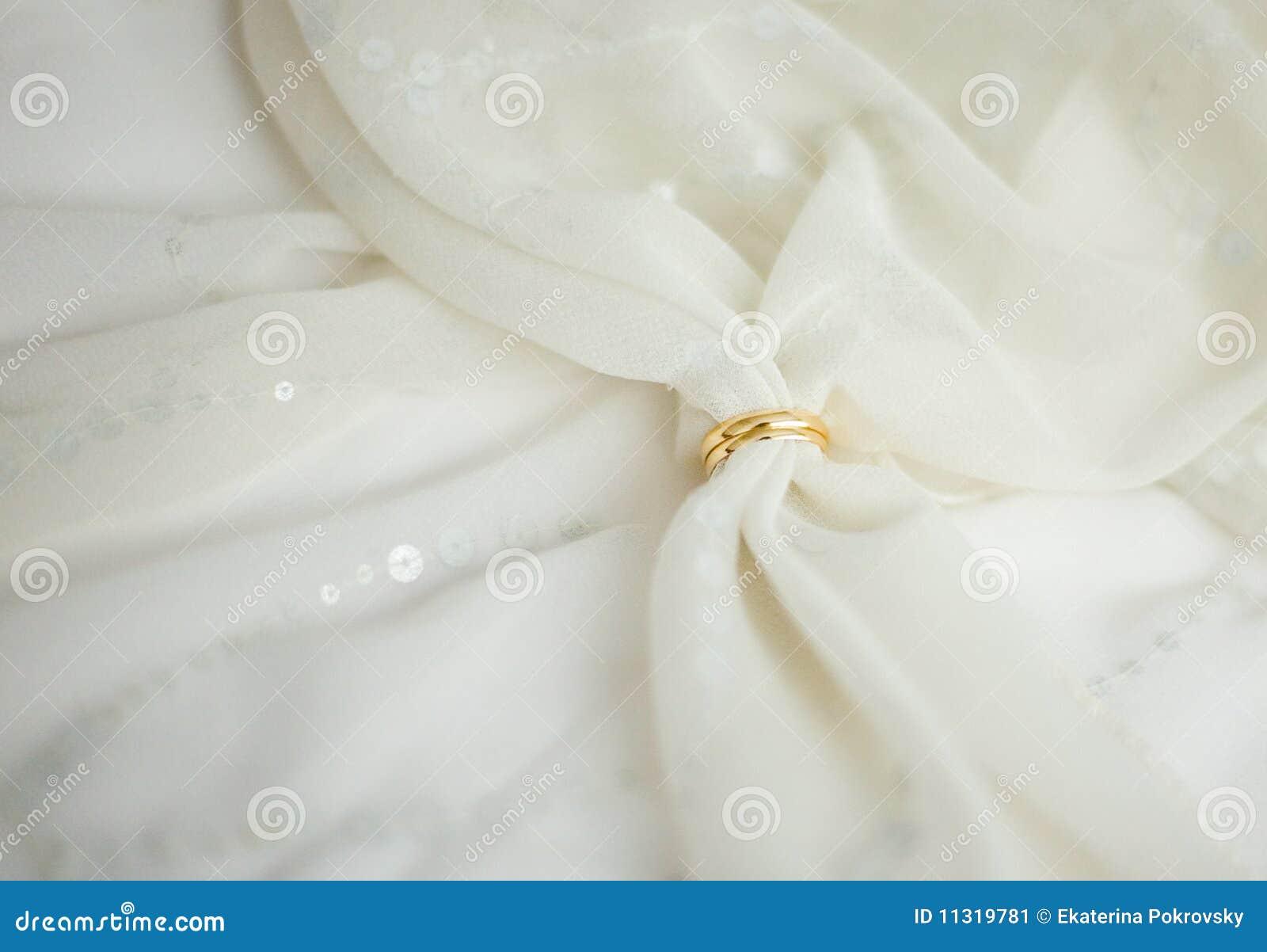 Zwei Ringe der goldenen Hochzeit mit Brautschleier