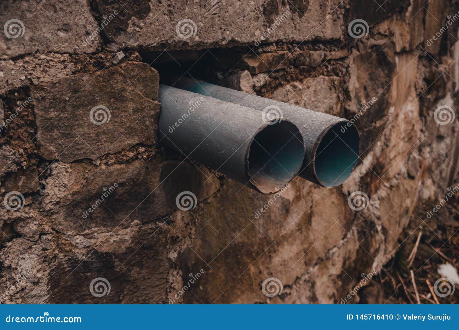 Zwei Rohre In Einem Loch Der Wand Stockfoto - Bild von