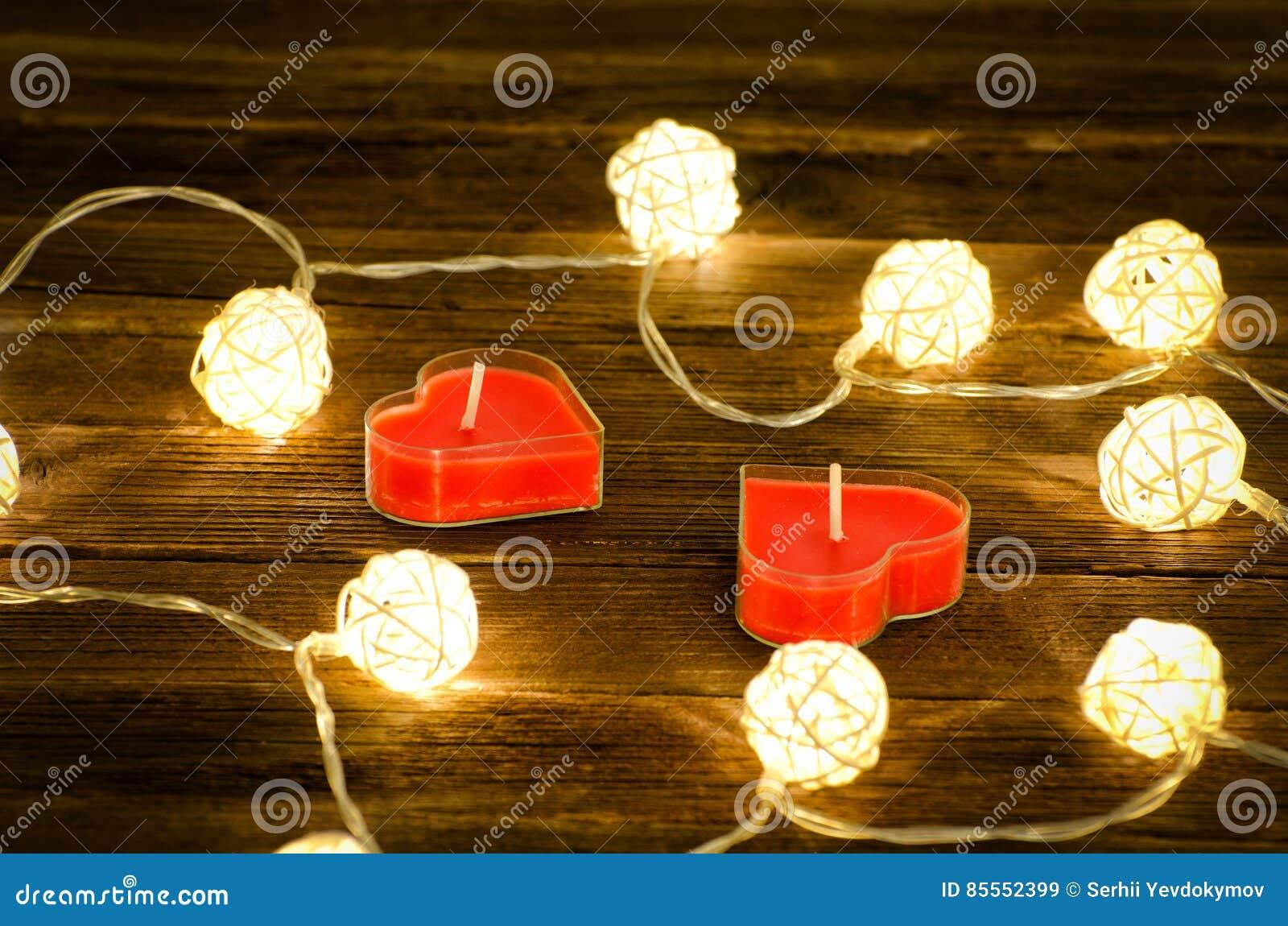 Zwei rote Kerzen in Form eines Herzens und glühenden Laternen hergestellt vom Rattan auf einem hölzernen Hintergrund Nahaufnahme