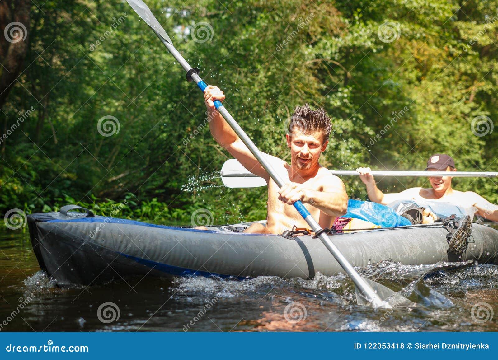 Zwei Ruderer im Boot mit Rudern in den Händen auf dem Fluss am Sommertag Jungesportkerle schwimmen ein Kanu entlang dem Fluss